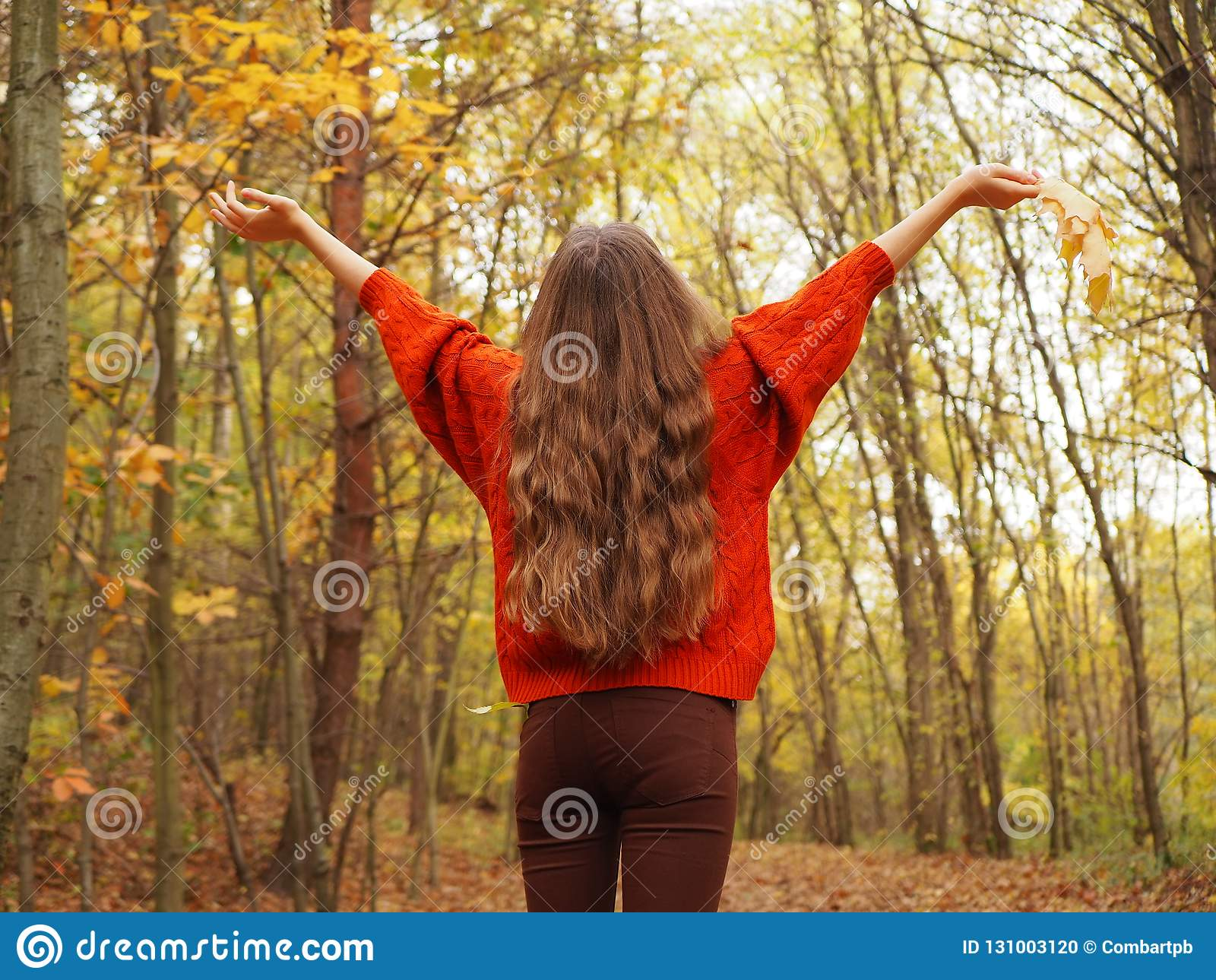 En tonåring som lyfter upp hennes händer med glädje En flicka som bär den orange tröjan och brun jeans