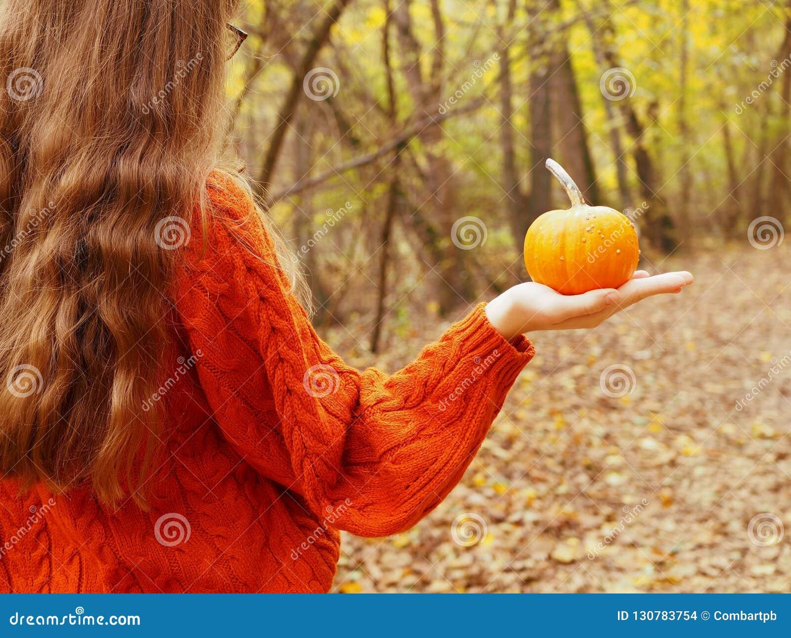 En tonårs- flicka som rymmer en pumpa i hennes hand som går i skogen