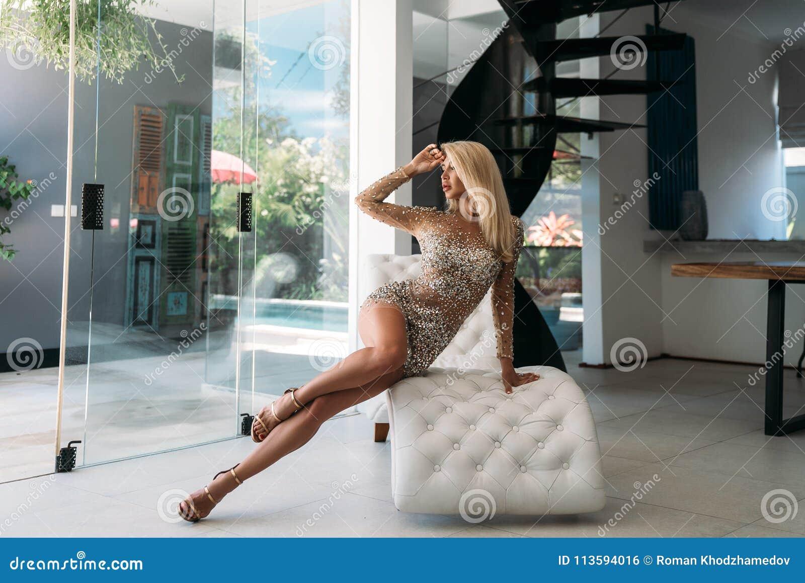 En trevlig flicka med ett härligt diagram i en kort skinande klänning vilar på en vit stilfull soffa i studion Stående av