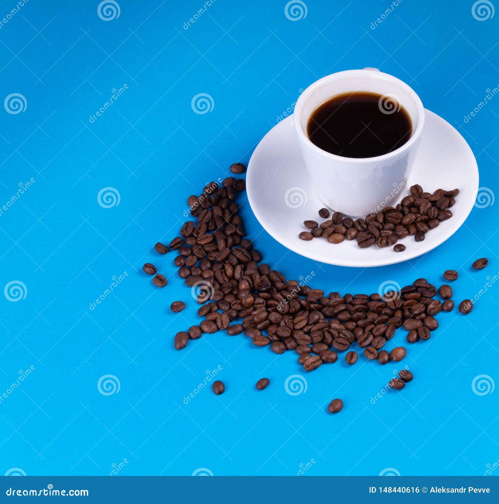 En un fondo azul, una taza de café al lado de ella se llena de los granos de café en la forma de un creciente