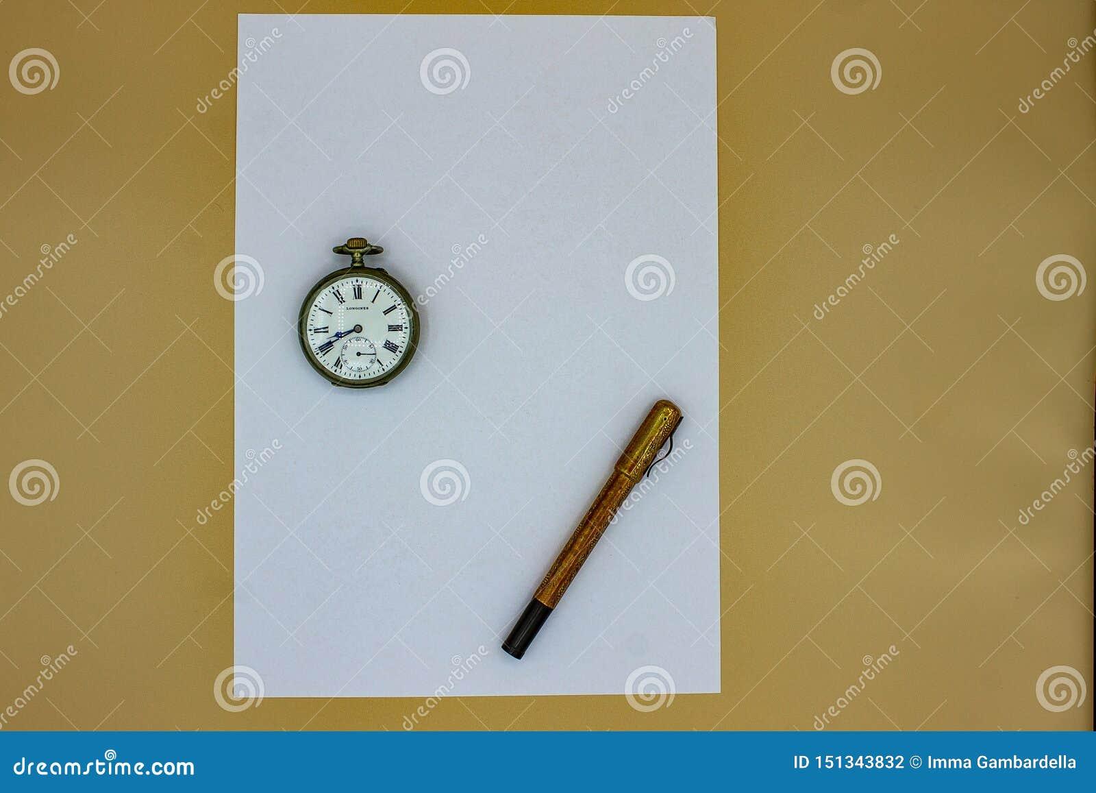 En una hoja blanca, una pluma del oro viejo y un reloj de bolsillo viejo La pluma y el reloj datan de los 1900s tempranos, de hec