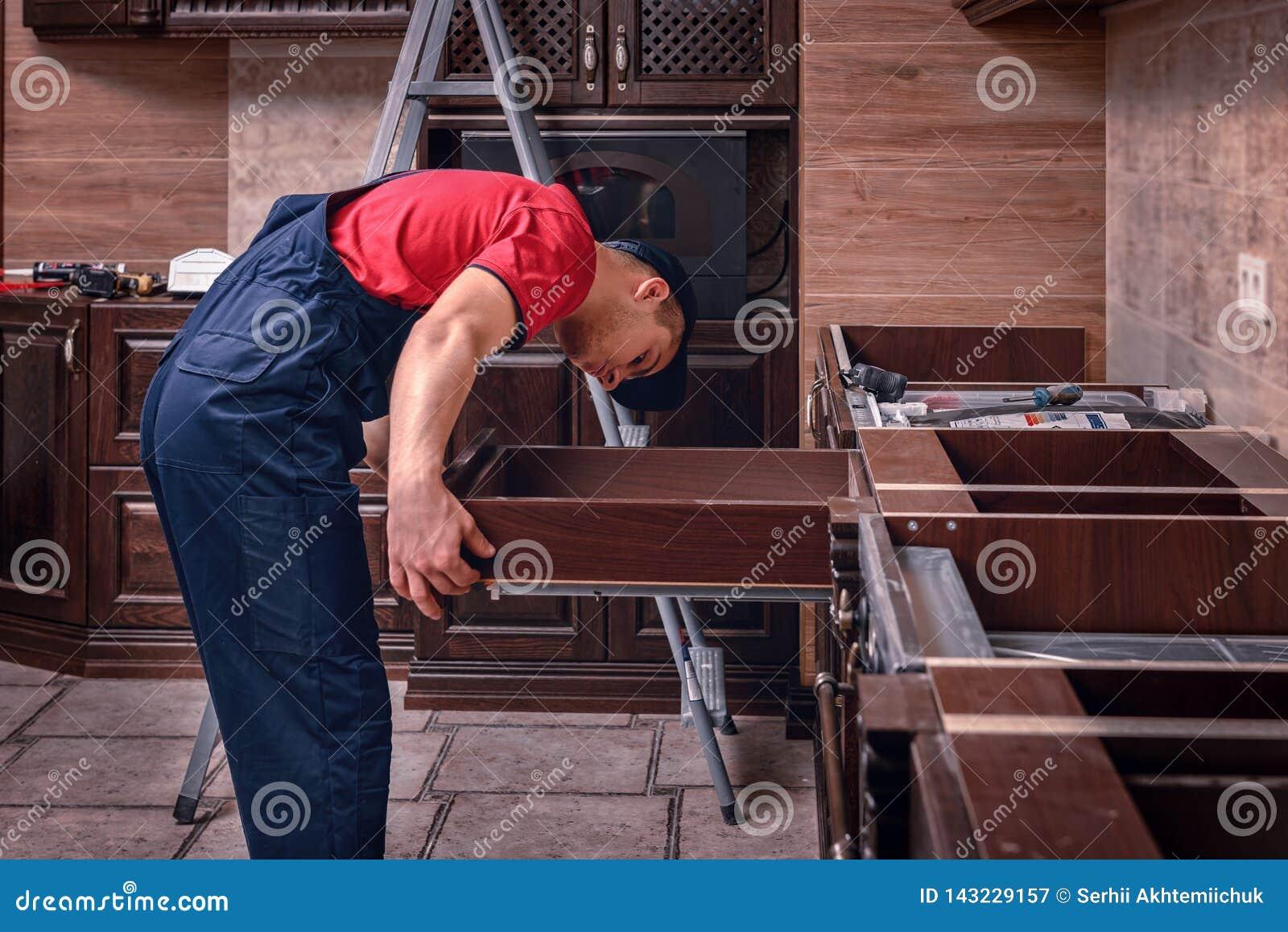 En ung arbetare installerar en enhet Installation av modernt träkökmöblemang