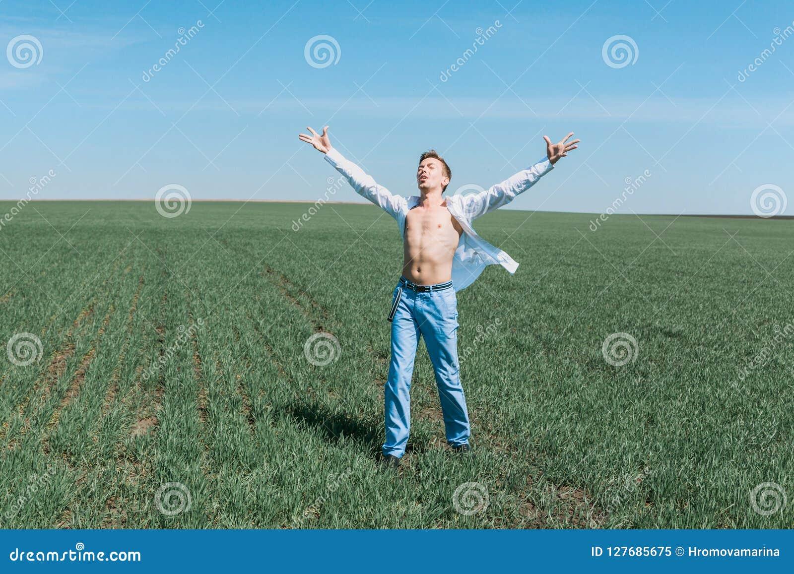 En ung attraktiv sportig man i en vit skjorta och jeans står i fältet