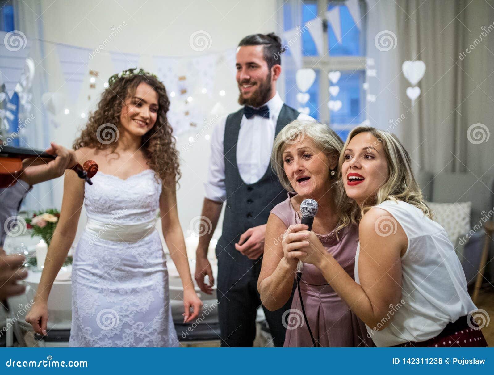 En ung brud och brudgum med andra gäster som dansar och sjunger på ett gifta sig mottagande