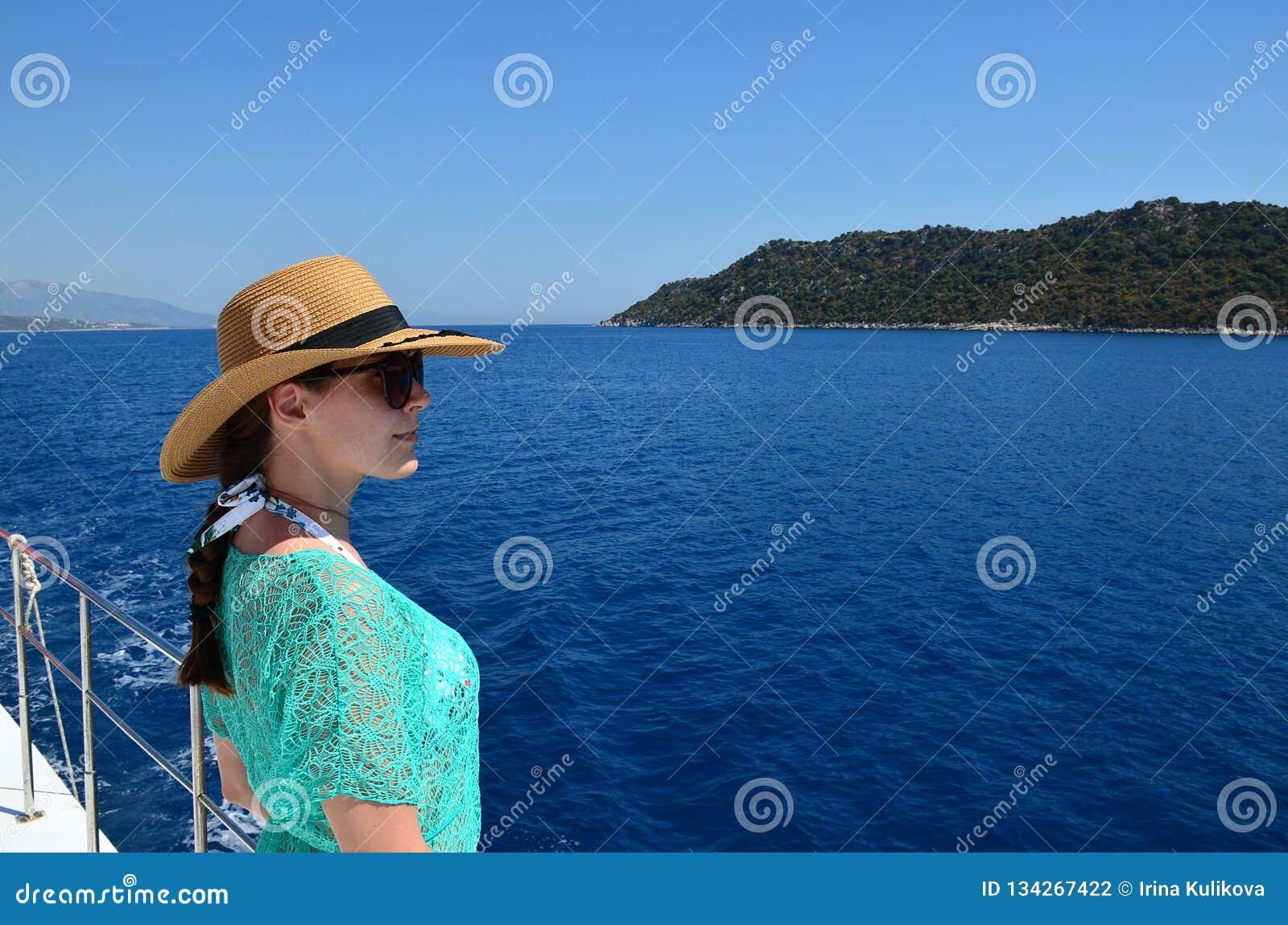 En ung brunettflicka i en sugrörhatt, solglasögon och en turkosstrandtunika ser bort mot bakgrunden av havet