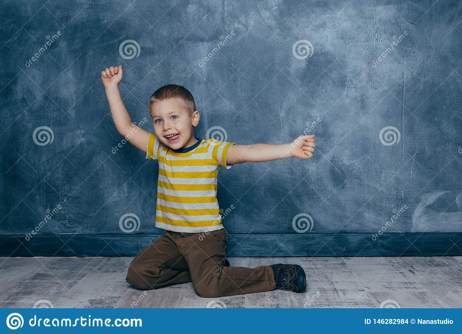 En ung emotionell pojke sitter p? ett tr?golv mot bakgrunden av en bl? v?gg i studion m?nskliga sinnesr?relser