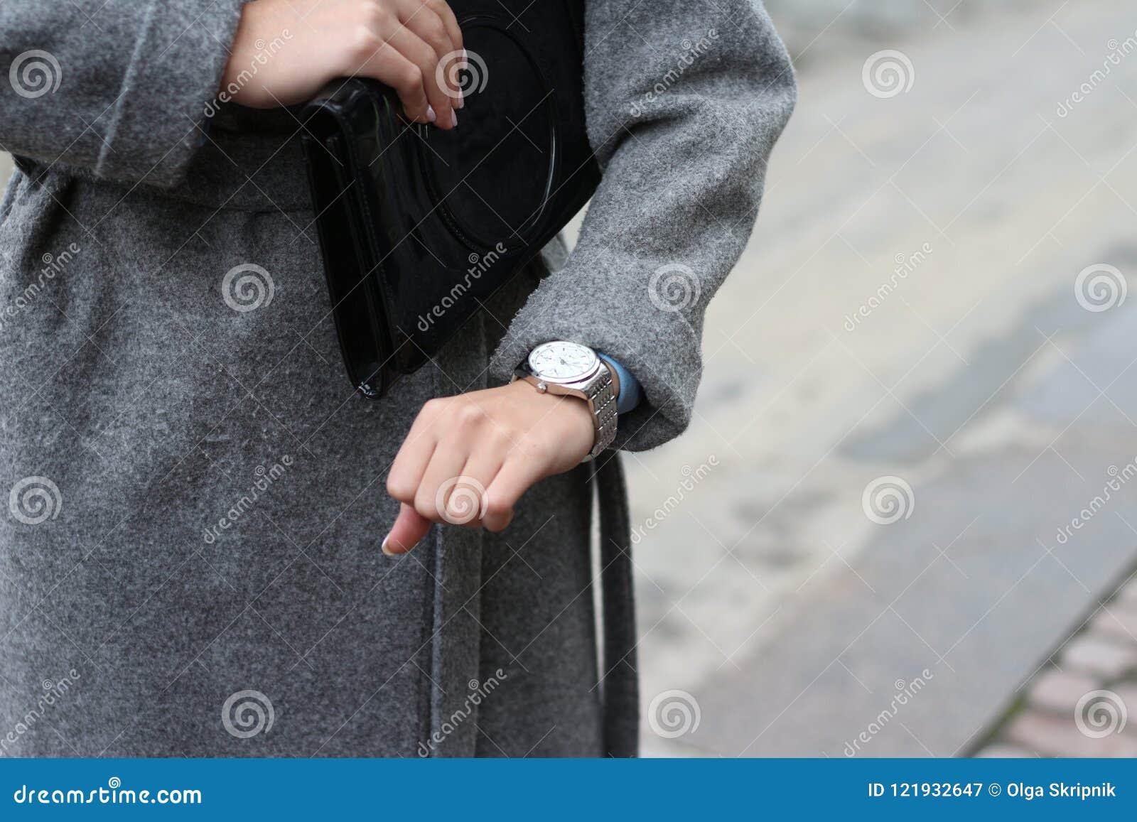 En ung flicka i ett grått lag ser hennes armbandsur, kontrollerar tiden, ser hennes klocka brådskan till ett möte, är sen punktli