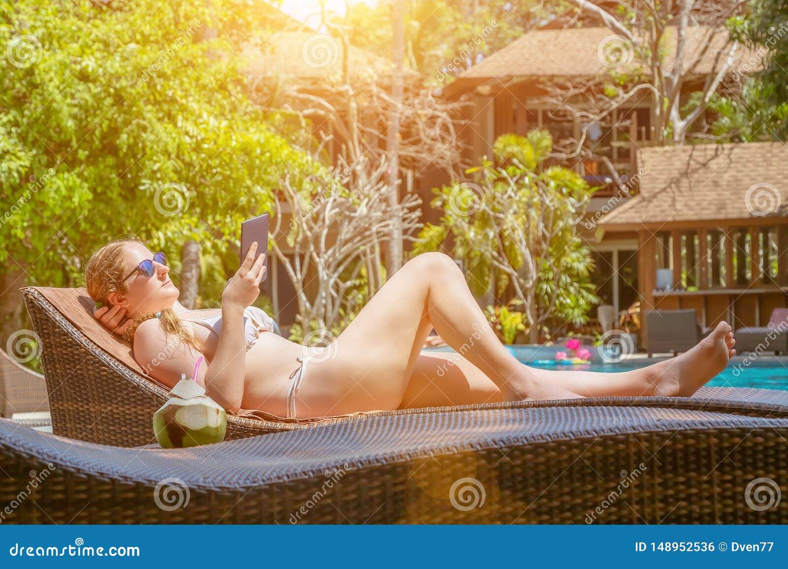 En ung flicka ligger p? en dagdrivare vid p?len och l?ser en eBook N?rliggande ?r ny kokosn?tfruktsaft Perfekt sommardag p?