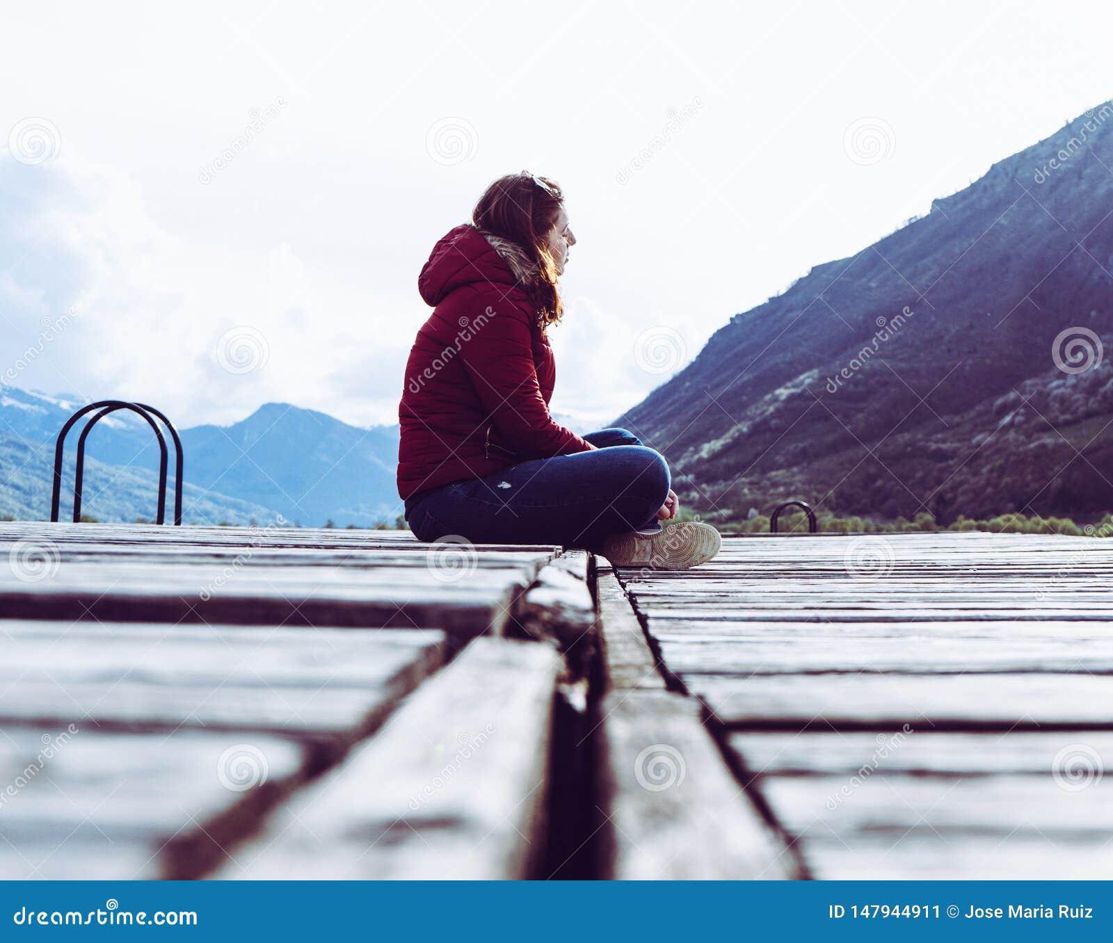 En ung flicka sitter p? kanten av en tr?pir och blickar in i avst?ndet som omges av berg i Plav sj?n