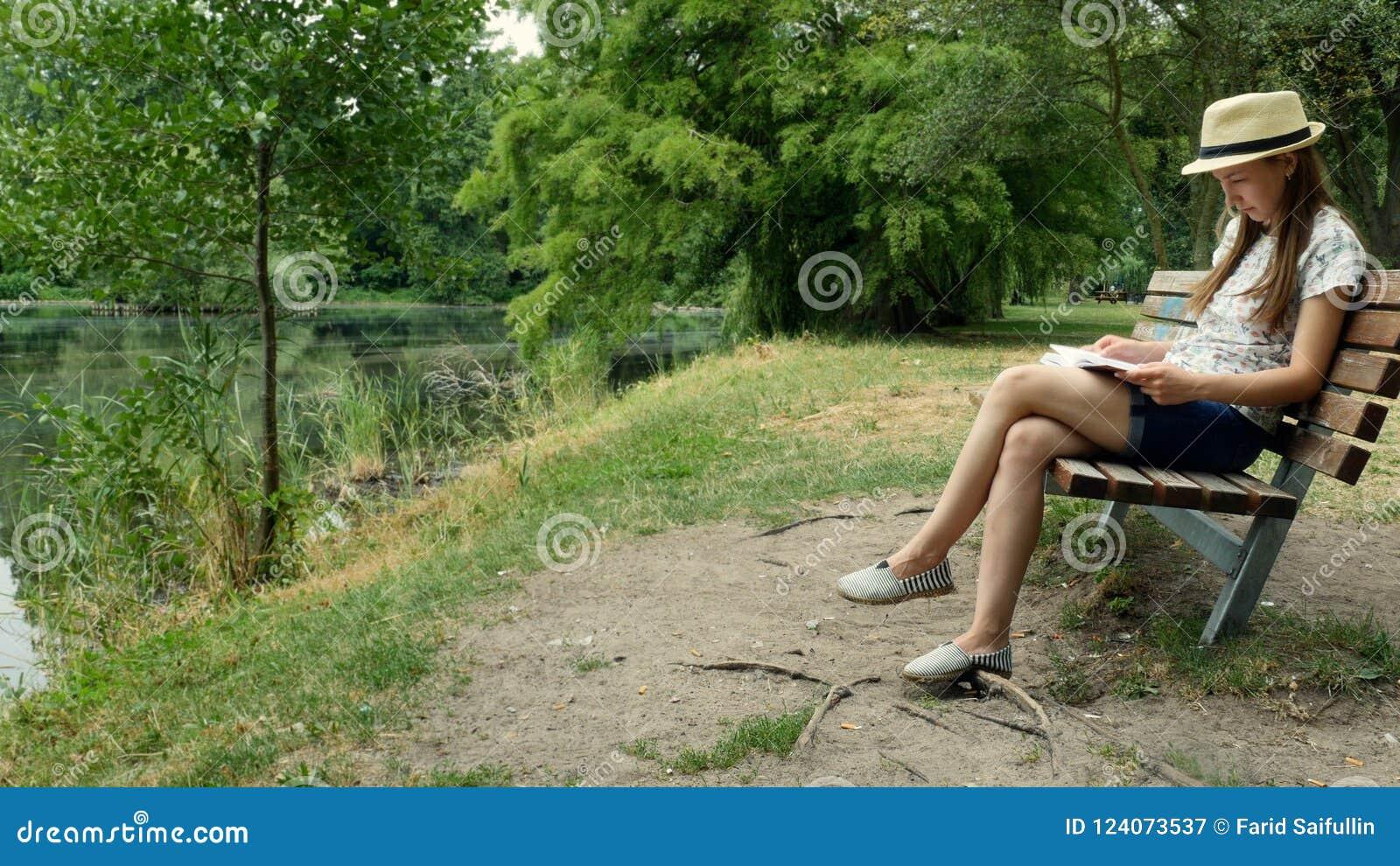 En ung flicka som läser en bok på en bänk nära sjön