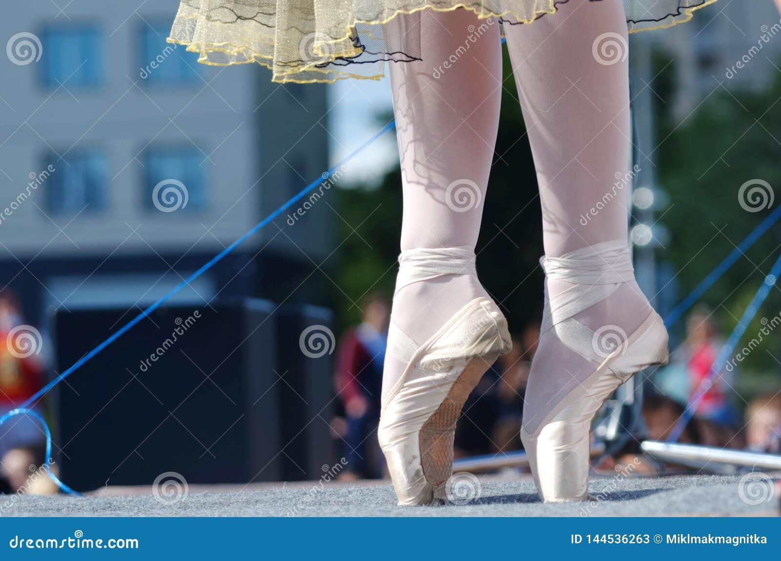En ung flicka står på pointe på en utomhus- gataplats Fritt tillträde för fotografi