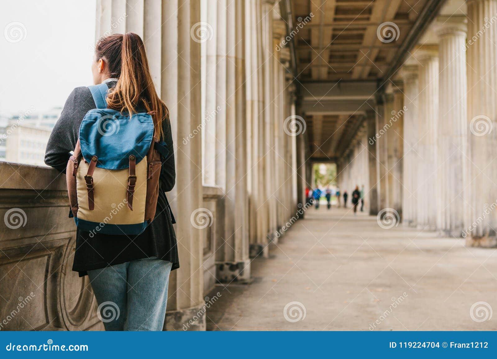 En ung flickahandelsresande eller en turist eller en student med en ryggsäck reser till Berdlin i Tyskland