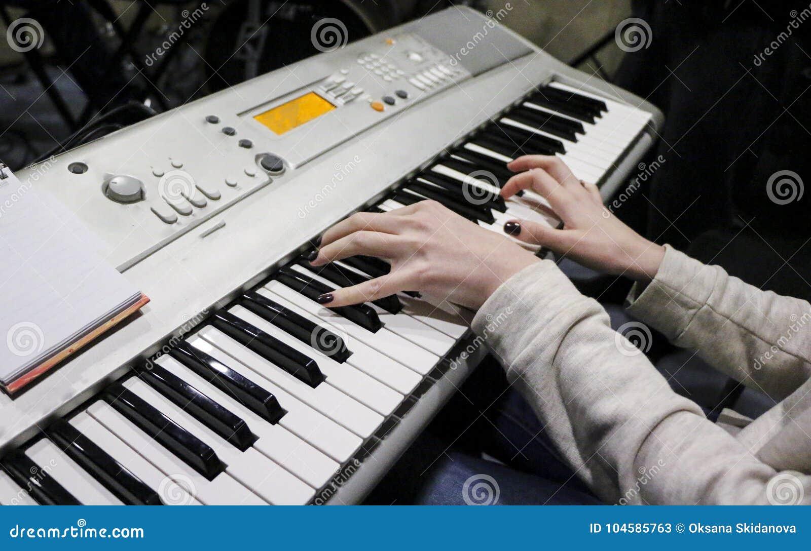 En ung flickapianist spelar det elektroniska pianot med hennes favorit- musik Kvinnliga behagfulla händer trycker på tangenterna
