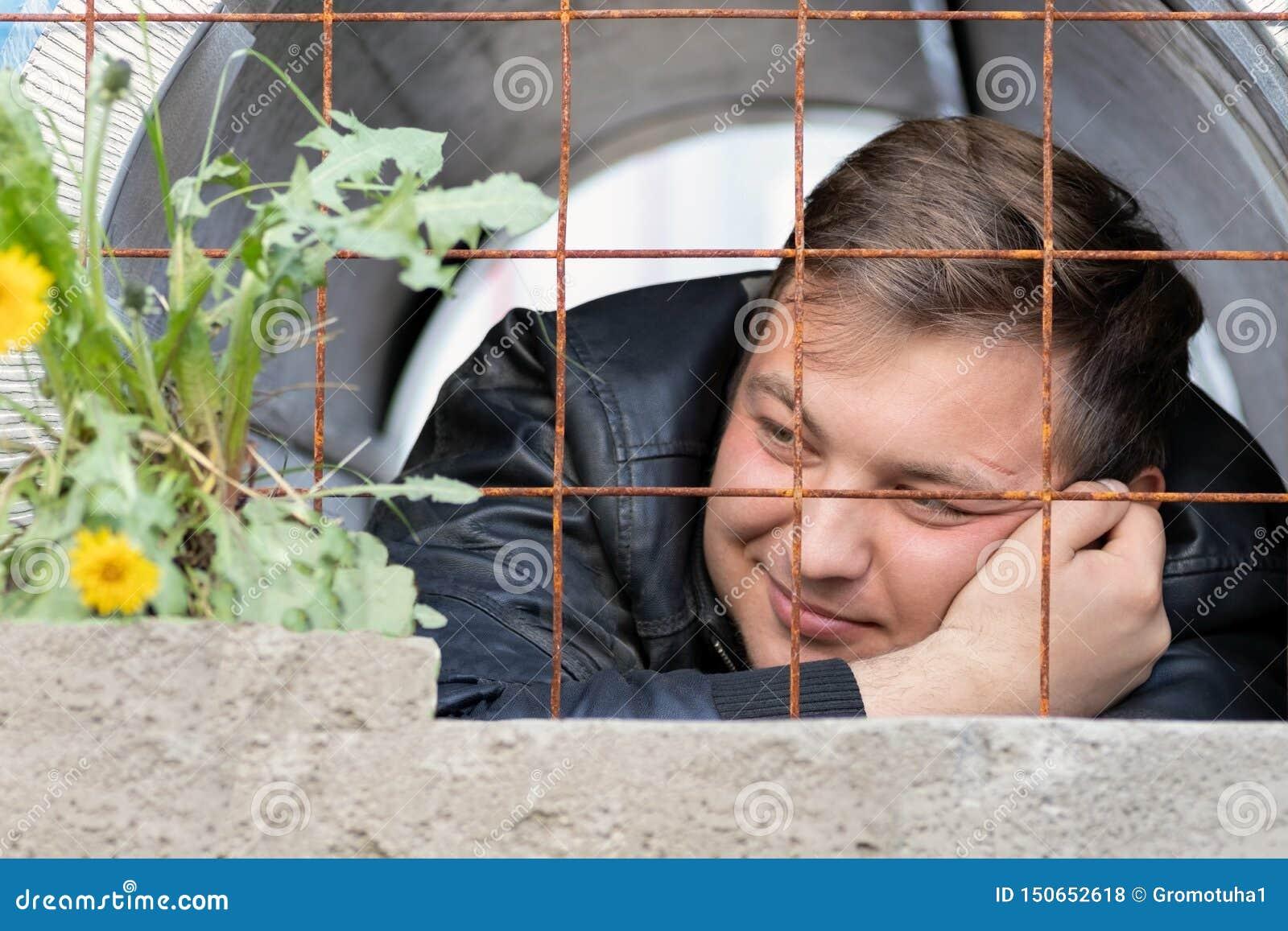 En ung grabb som sitter i fängelset som ser växa bak en rostig gallermaskrosblomma Fångedrömmarna av frihet från