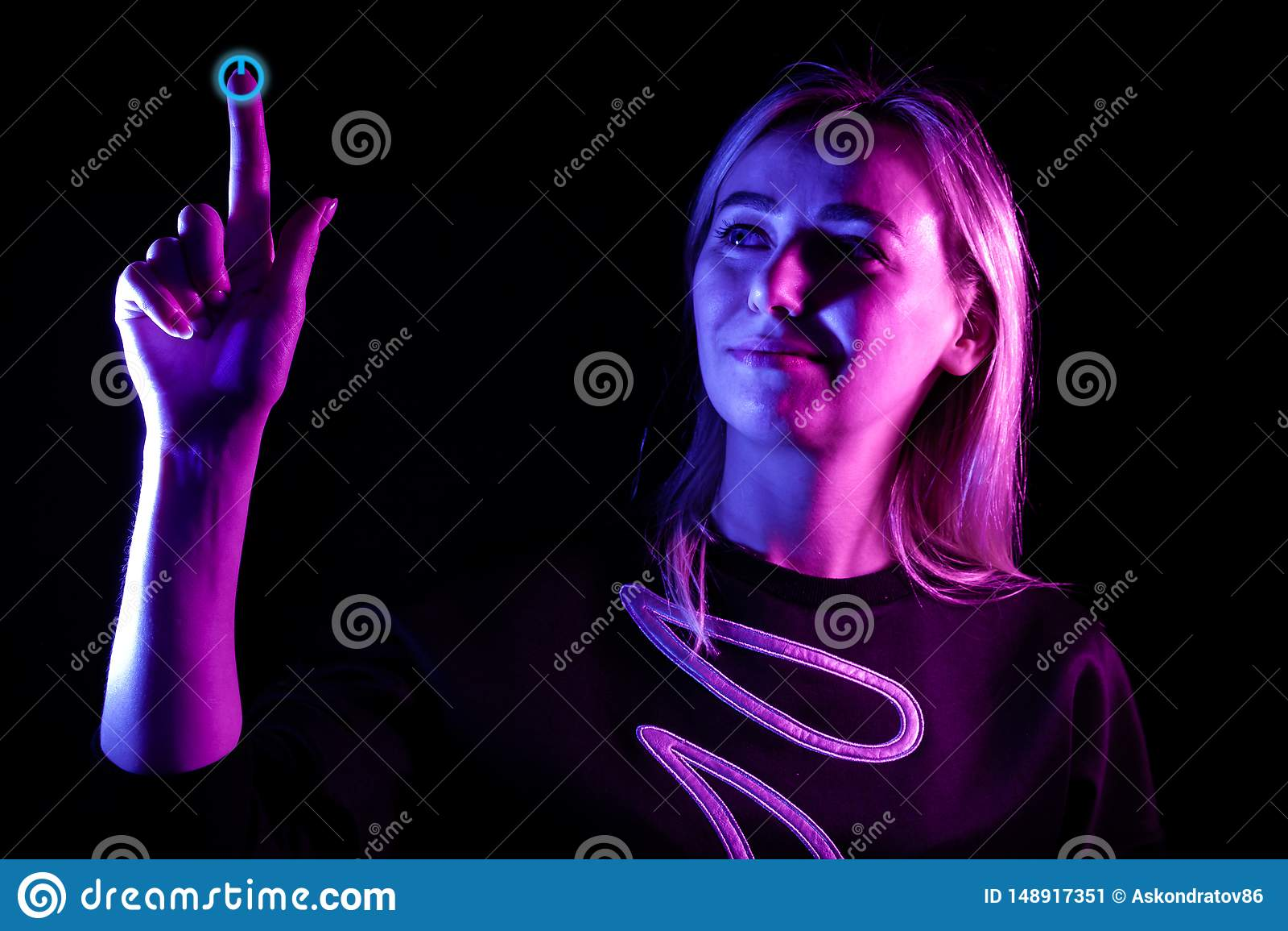 En ung h?rlig flickablondin markerade i bl?tt, och rosa p? sidorna lyfter hennes hand till ?verkanten och trycker p? p? maktknapp