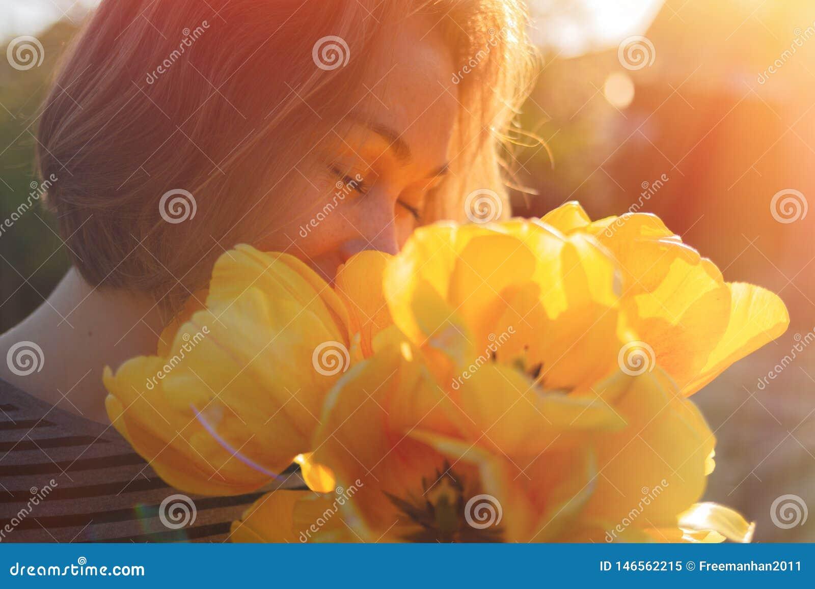 En ung kvinna inhalerar doften av vårblommor, gula tulpan Begrepp av allergin close upp