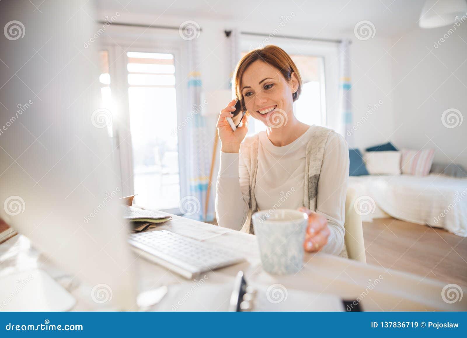 En ung kvinna med datoren och smartphonen inomhus och att arbeta i en inrikesdepartementet