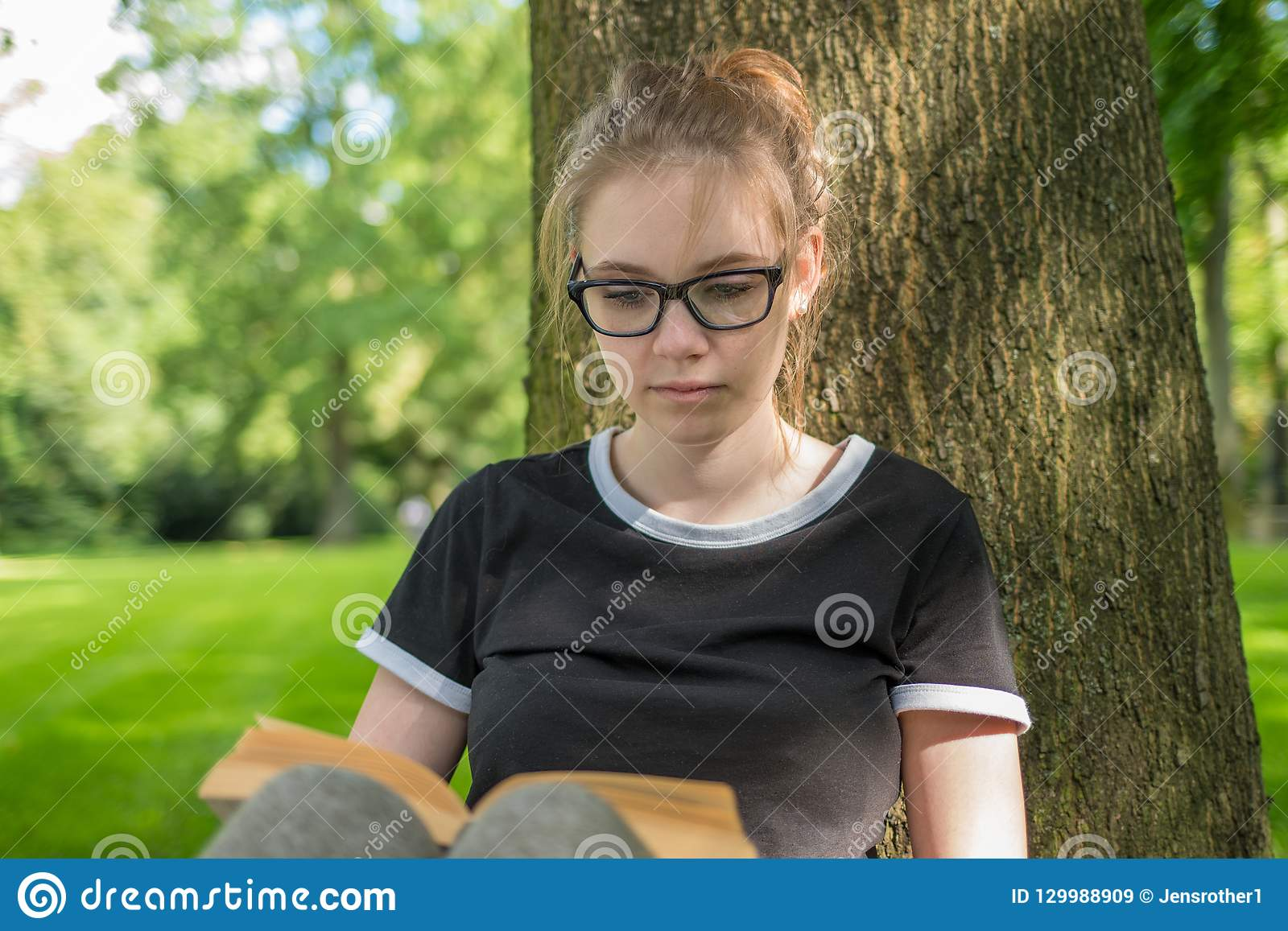 En ung kvinna sitter under ett träd i parkerar och läste en bok