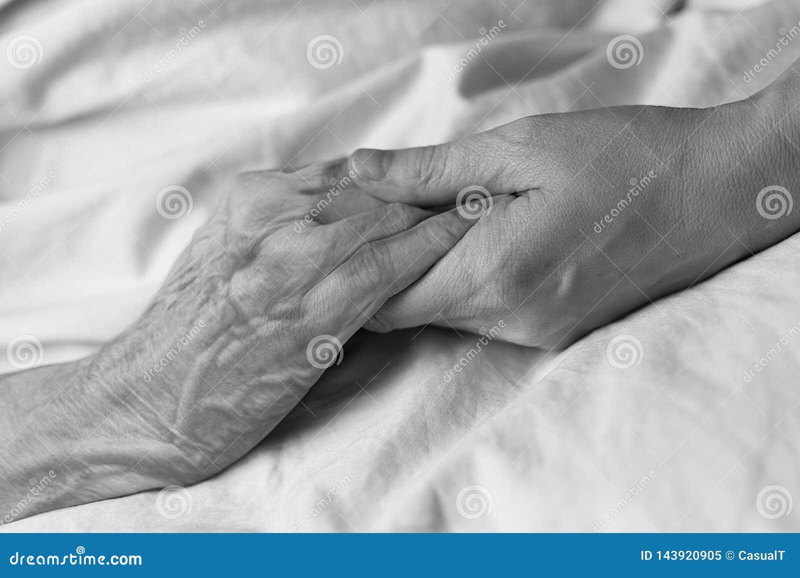 En ung kvinna som rymmer handen av en gammal kvinna i en sjukhussäng, svart & vitt