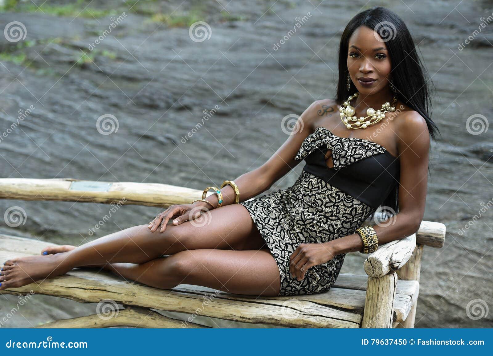 En ung kvinnlig afrikansk amerikankvinna som bär den eleganta klänningen som poserar i parkera