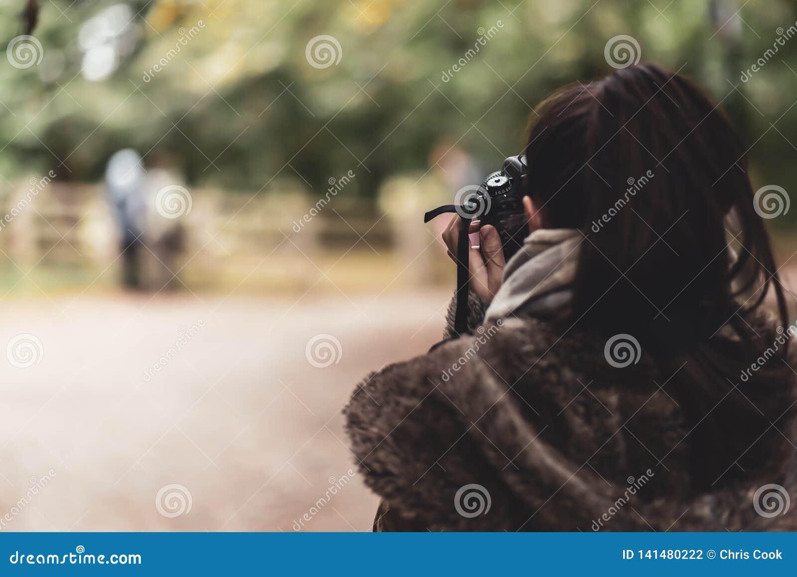 En ung kvinnlig caucasian fotograf tar en bild av ett par