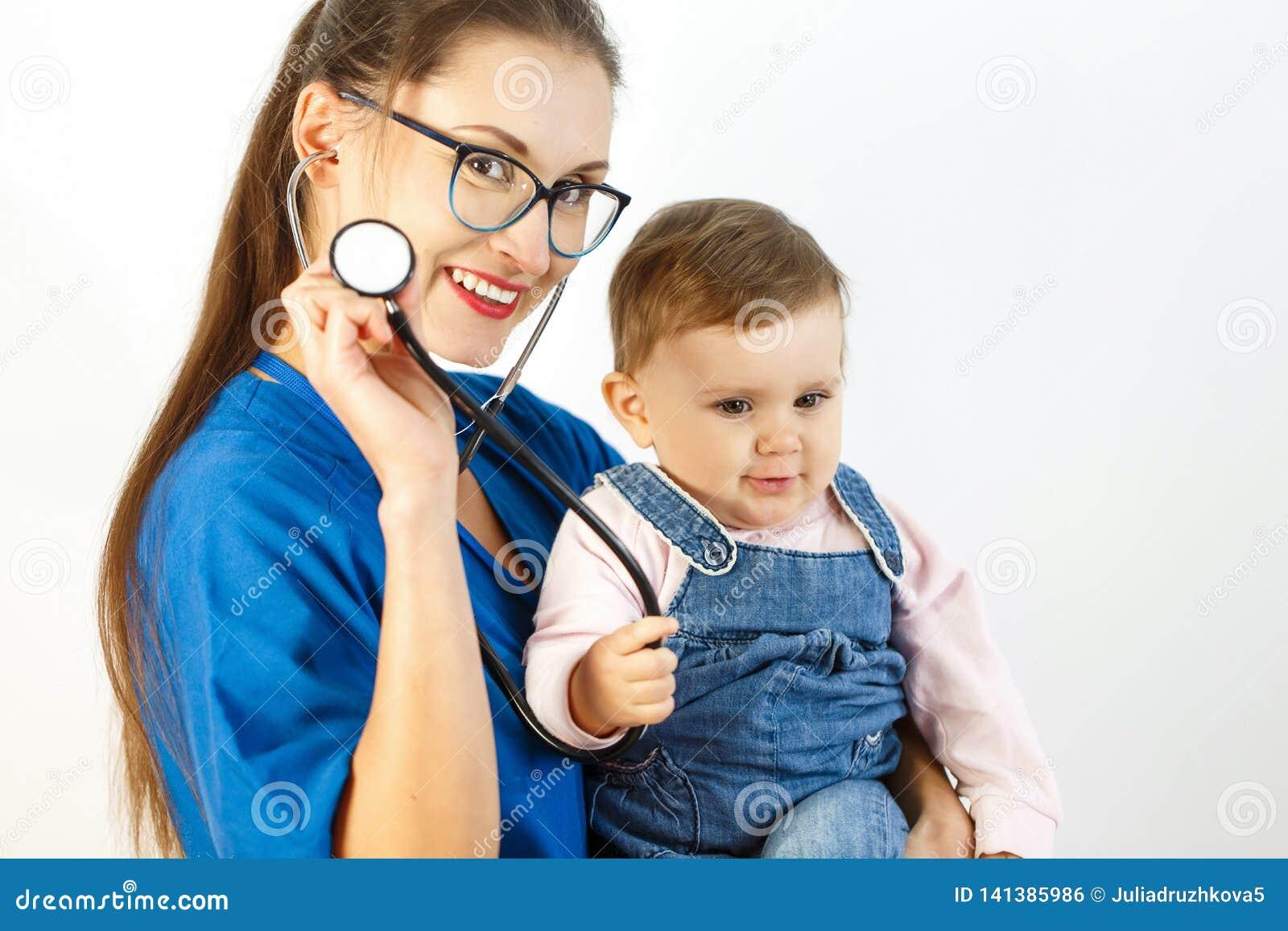 En ung kvinnlig doktor rymmer behandla som ett barn i hennes armar, och behandla som ett barn ler på en stetoskop Vit bakgrund