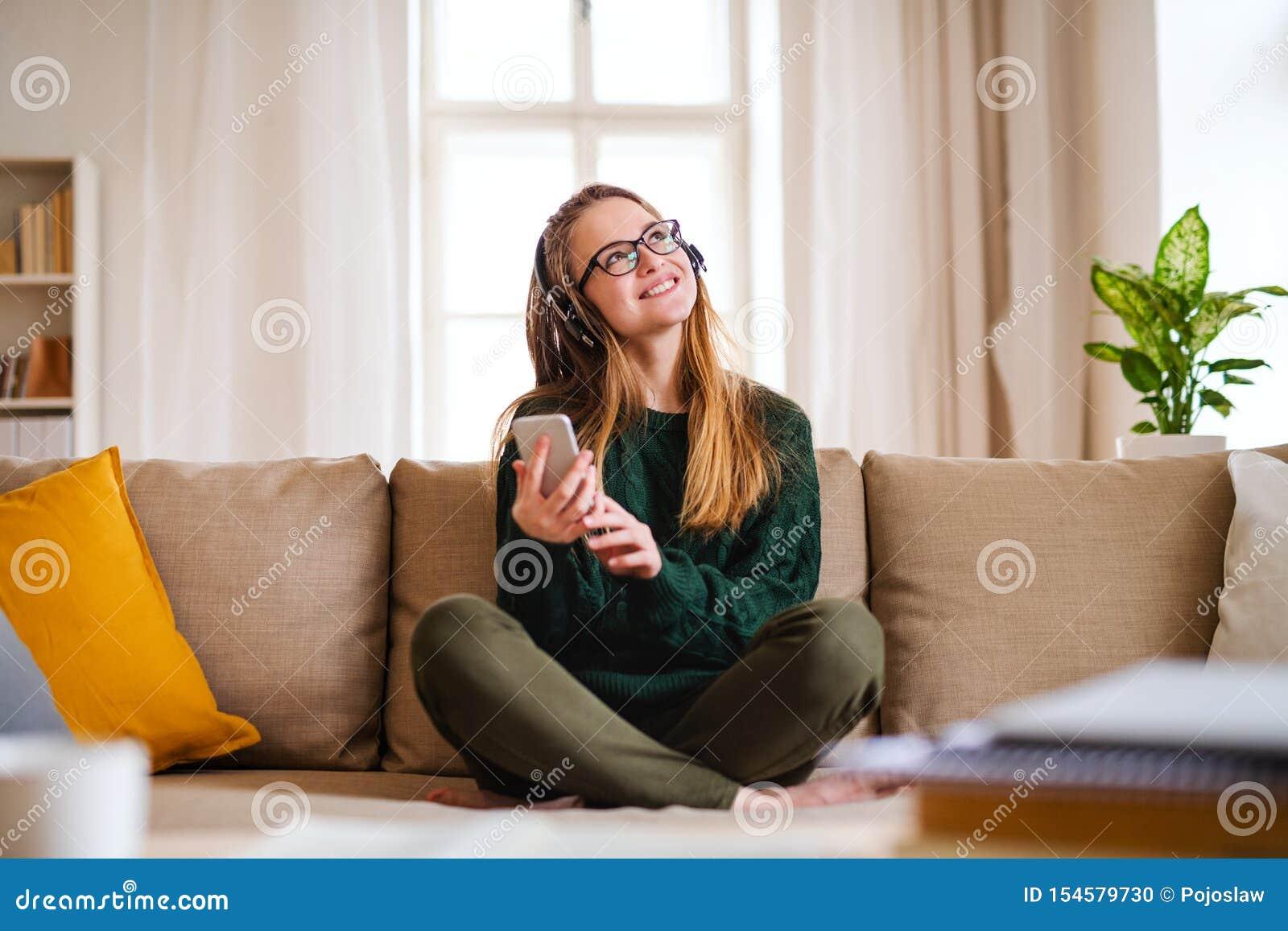 En ung kvinnlig student som sitter p? tabellen, genom att anv?nda h?rlurar, n?r studera