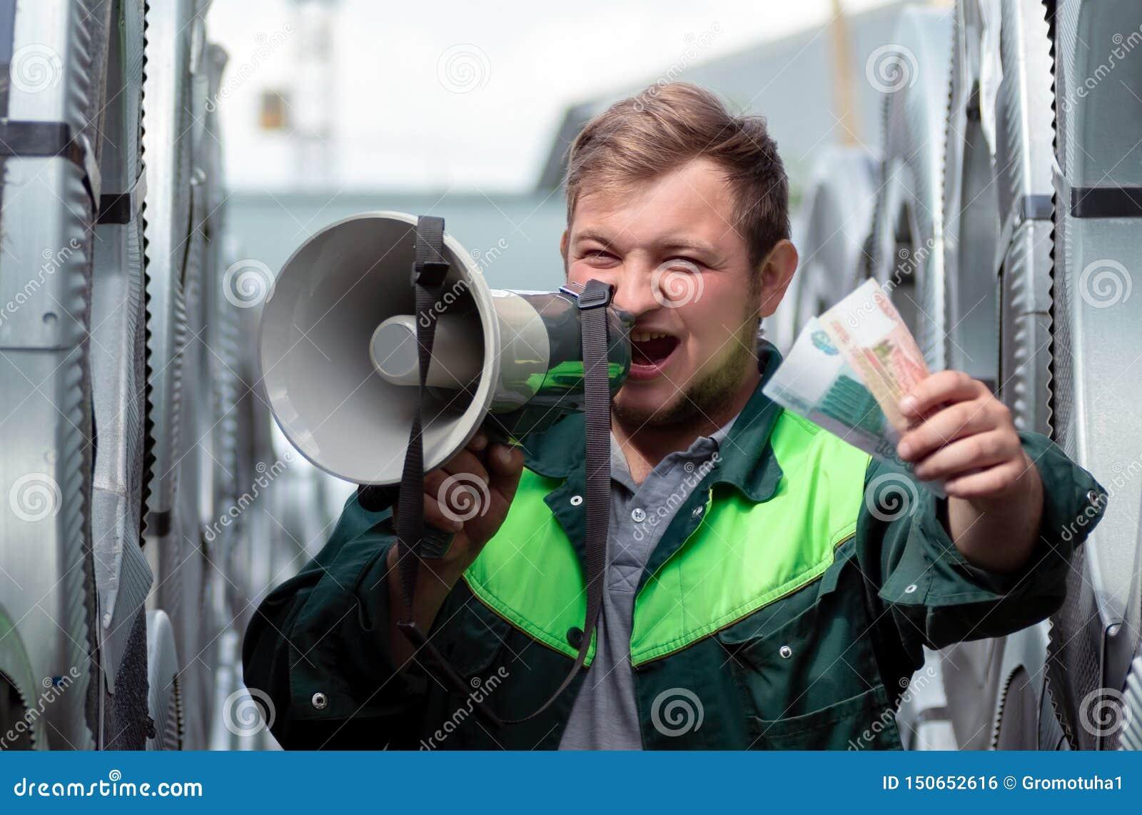 En ung man i arbetskläder ropar högt in i en högtalare som inviterar för att sammanfoga honom på arbete Mannen rymmer ut sedlar s