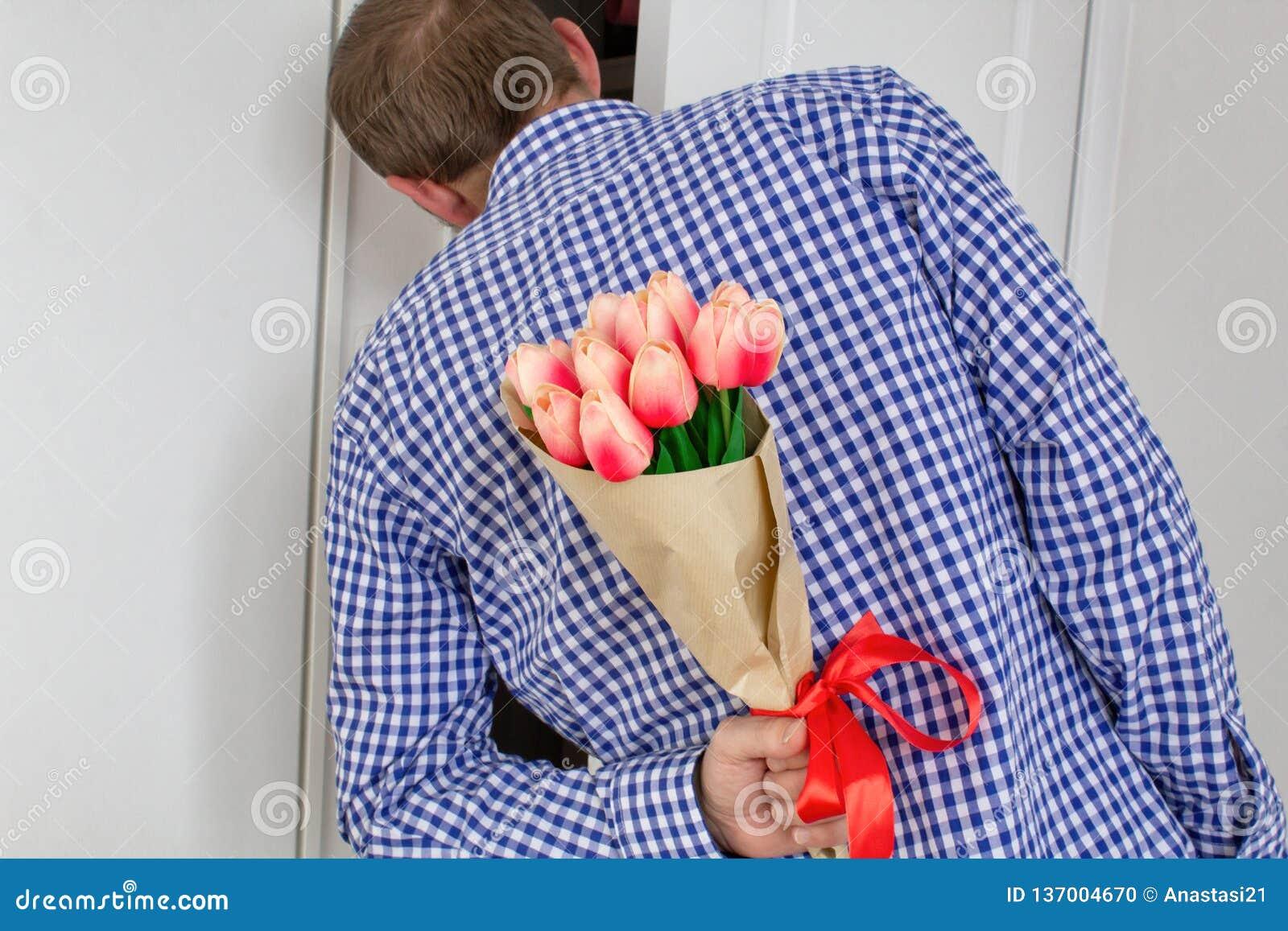 En ung man i en blå plädskjorta och jeans som rymmer en bukett av tulpan bak hans baksida och tittar i den öppna dörren