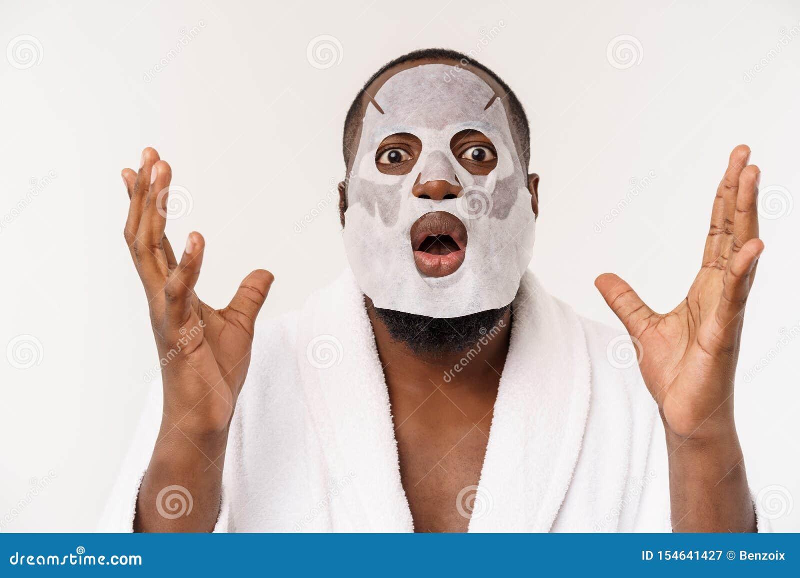En ung man med den pappers- maskeringen på framsidan som ser chockad med en öppen mun som isoleras på en vit bakgrund