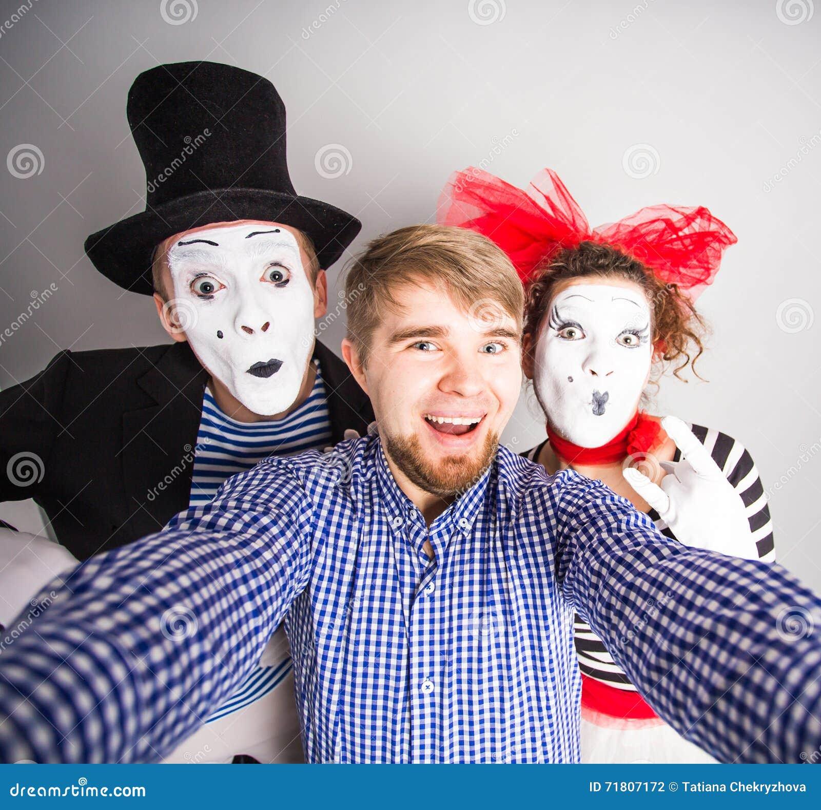 En ung man och ett roligt par av fäders som tar ett selfiefoto