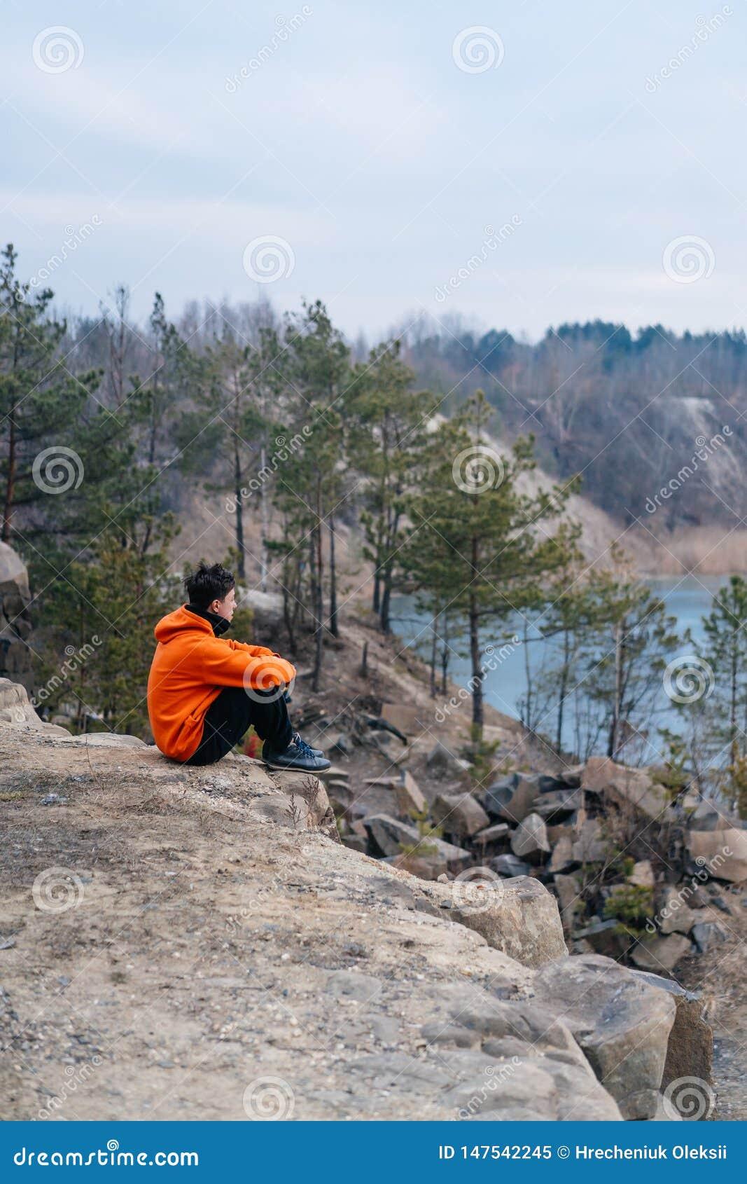 En ung man som sitter på kanten av en klippa, poserar för kameran
