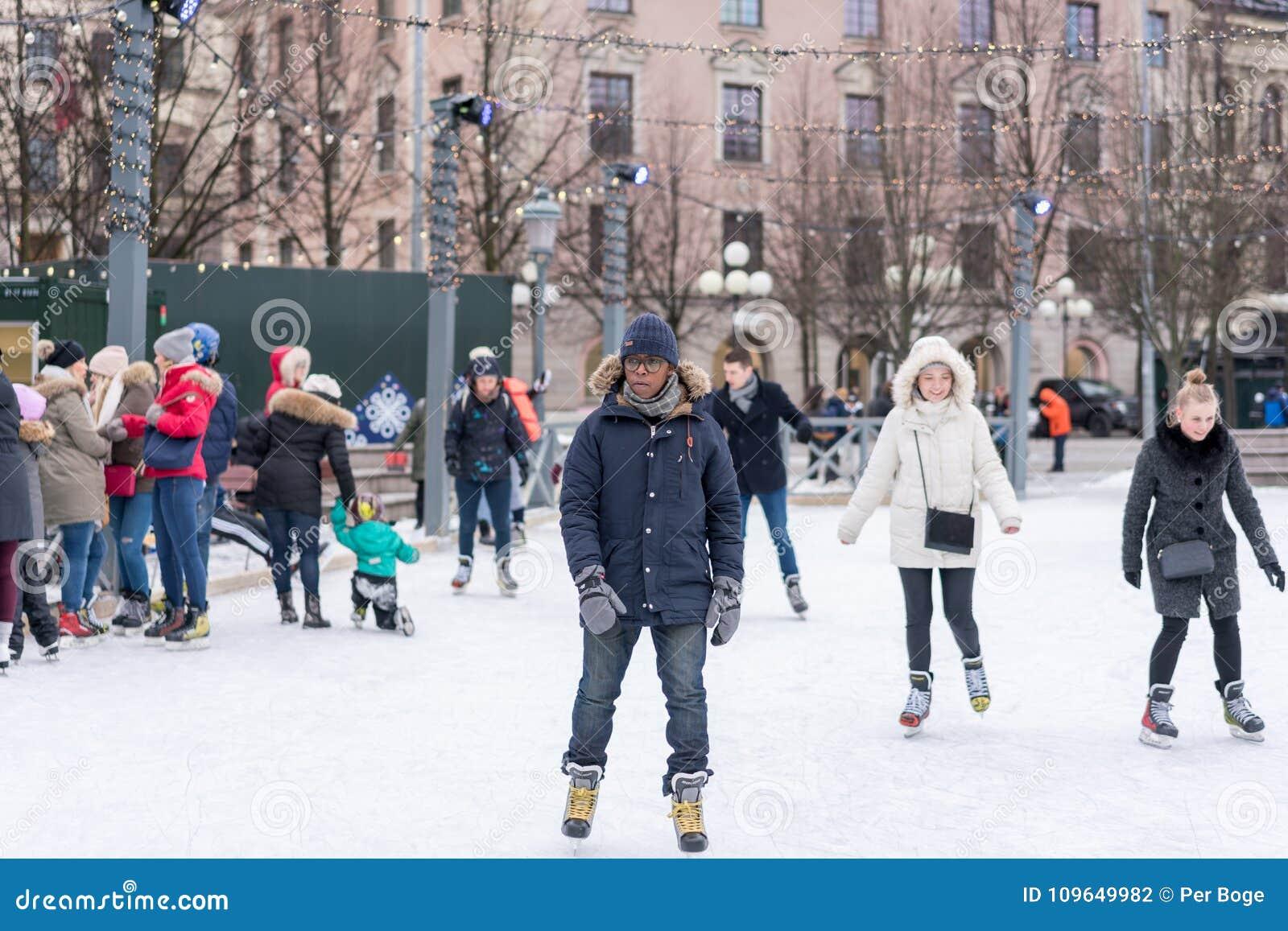 En ung man som utomhus åker skridskor på en offentlig skridskoåkningisbana i staden