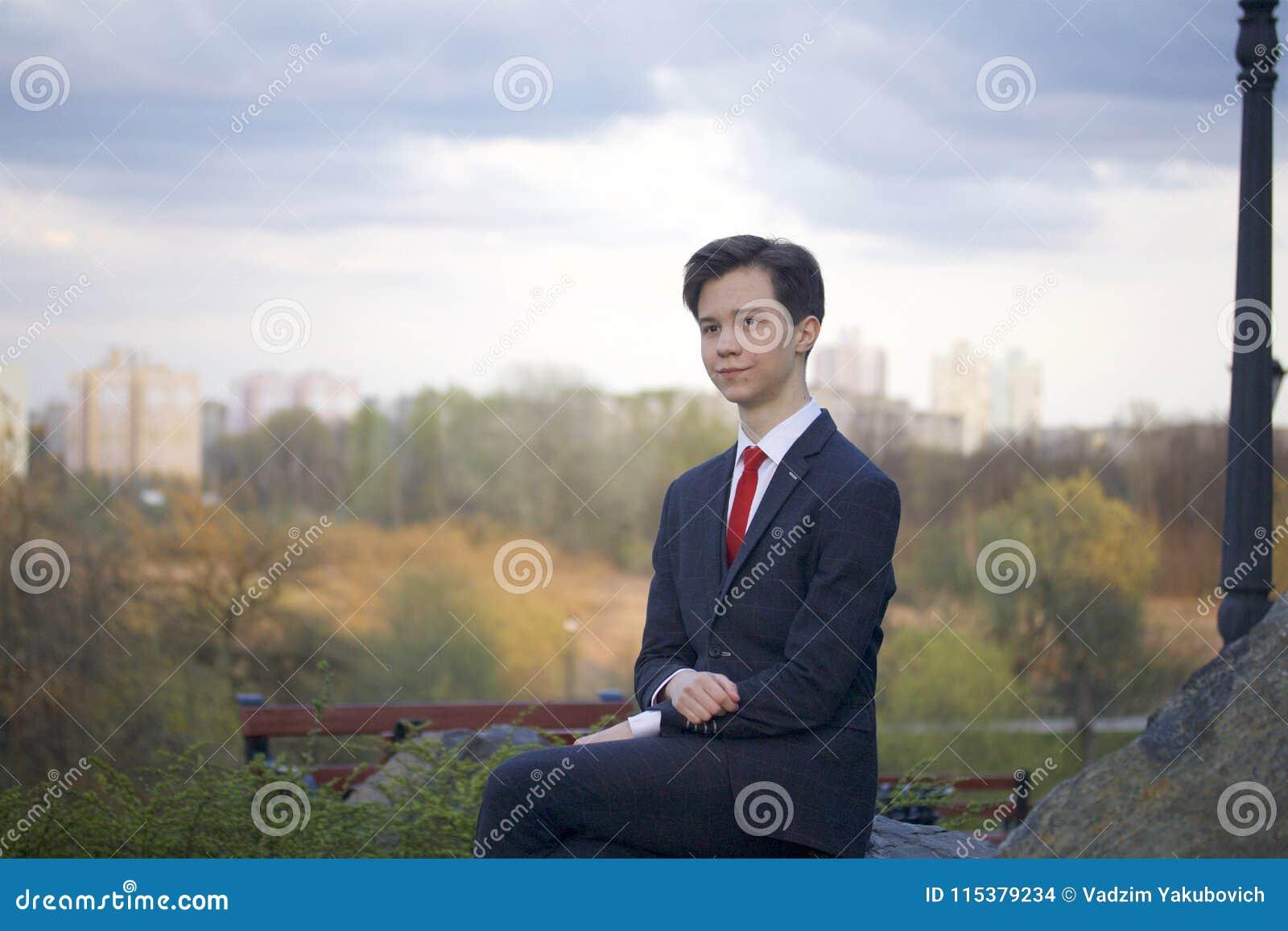 En ung man, en tonåring, i en klassisk dräkt Han sitter på en stor stenblock i en vår parkerar, hans händer som knäppas fast på h