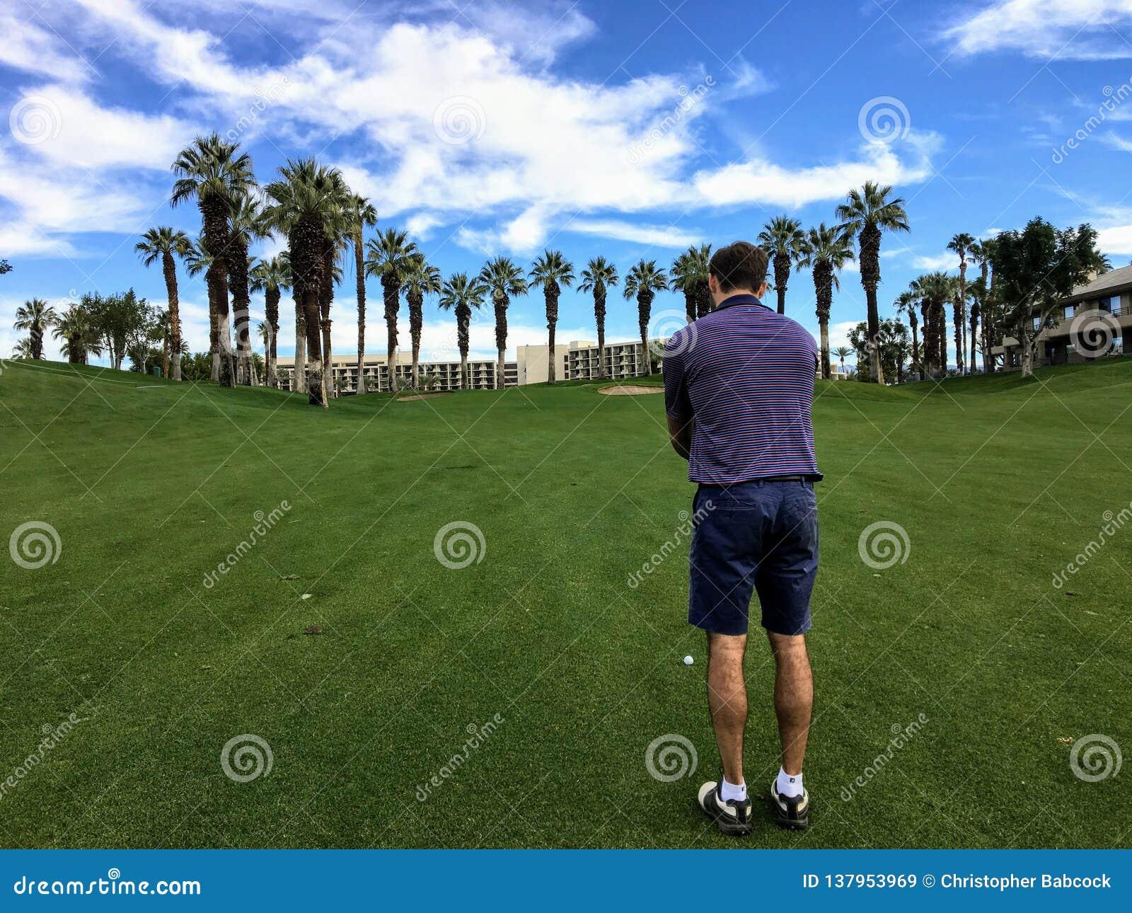 En ung manlig golfare som ställer upp hans inställningsskott från mitt av farleden på en medeltal 4 på en golfbana i Palm Springs