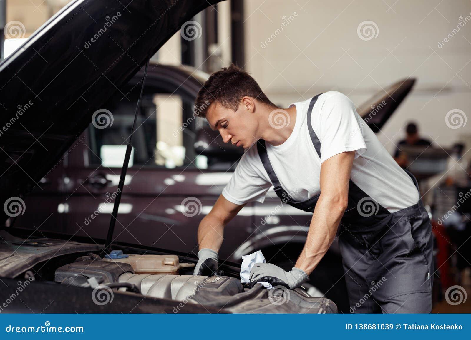 En ung och snygg mekaniker gör hans jobb på en bilservice