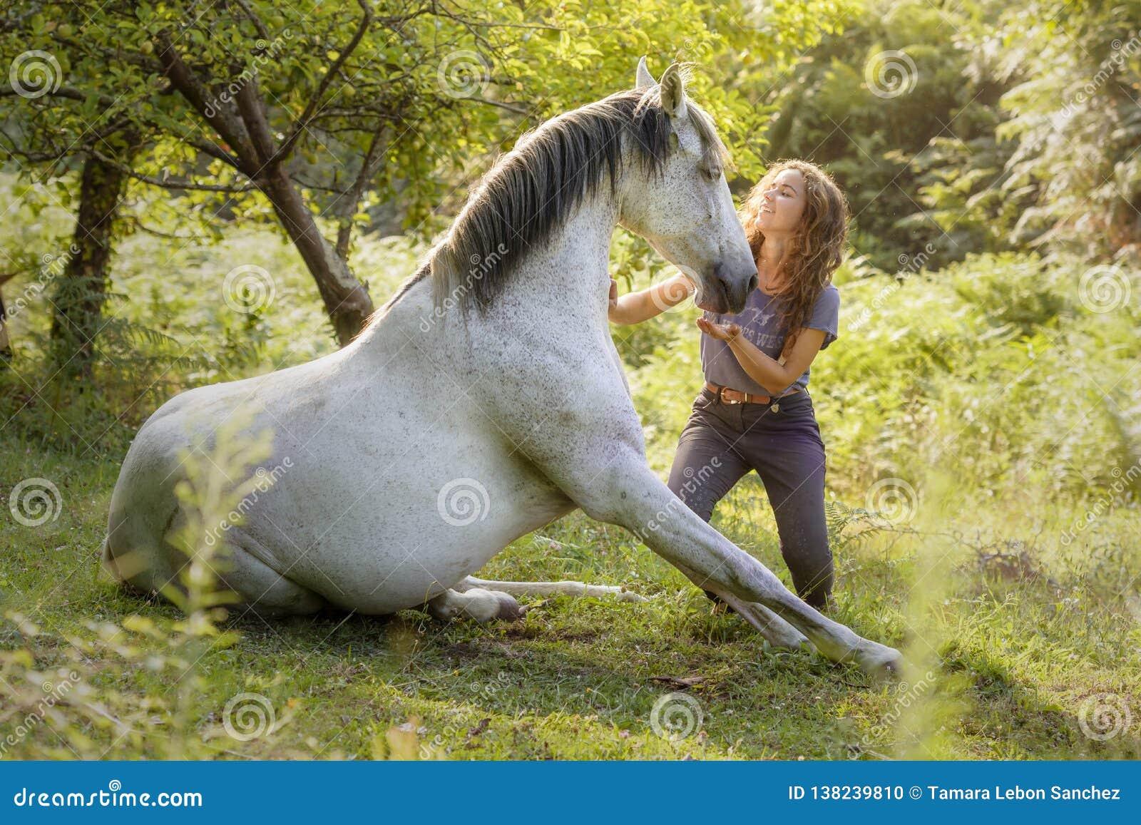 En ung skicklig ryttarinna visar ett trick med hennes häst utbildad med naturlig dressyr som introducerar oss i världen av ridkon