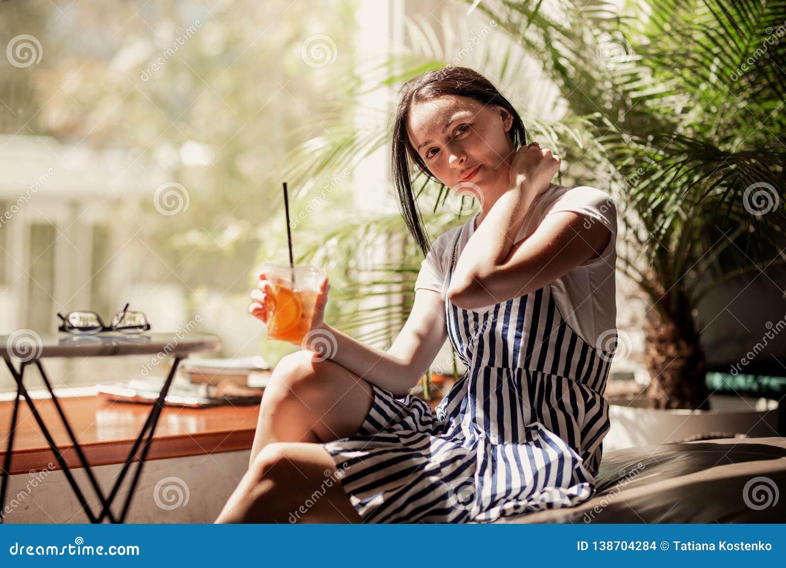 En ung slank le flicka med mörkt hår, iklädd tillfällig dräkt, sitter på tabellen och dricker kaffe i ett hemtrevligt kaffe