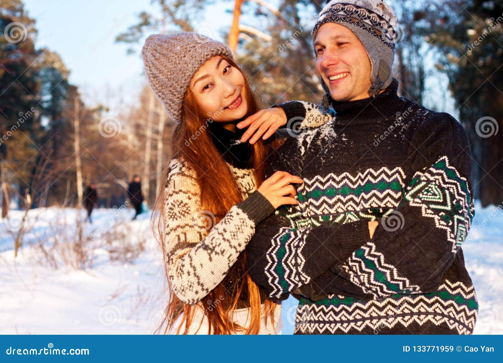 En ung stilig man av det europeiska utseendet och en ung asiatisk flicka i parkerar på naturen i vinter
