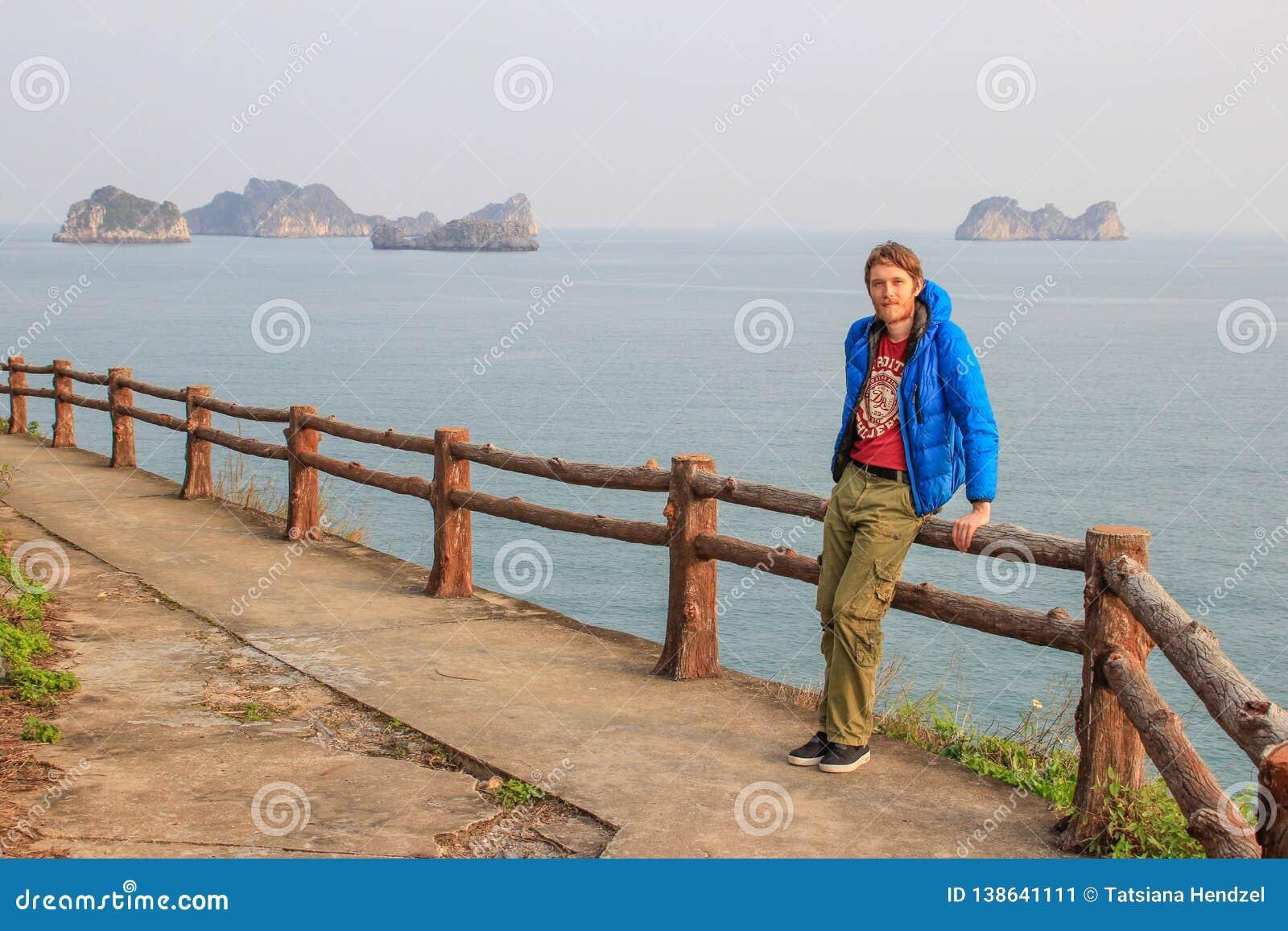 En ung vit attraktiv man som är blond med ett skägg i en blått ner omslagsställningar mot bakgrunden av en klippa och havet i mum