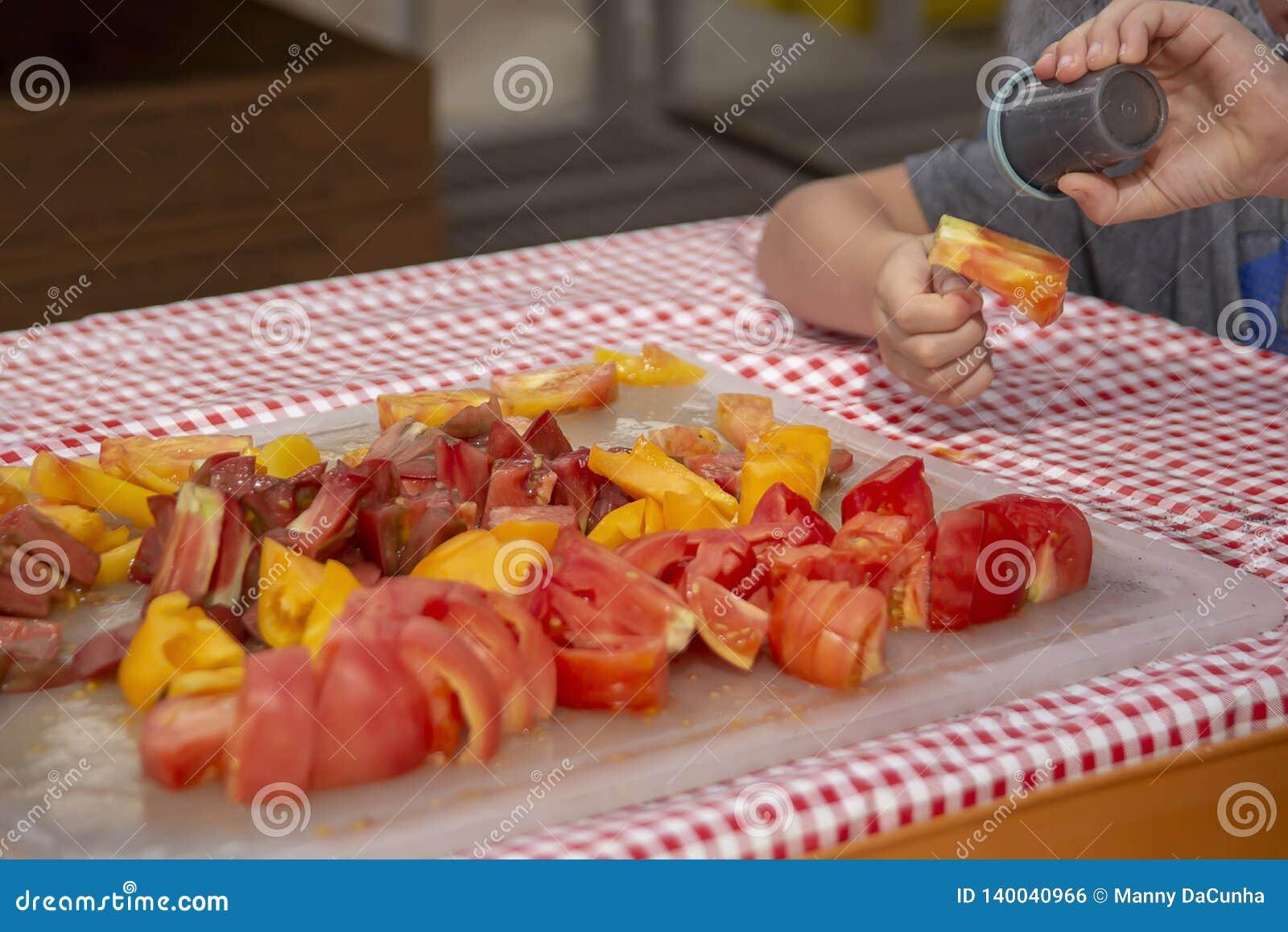 En unge tycker om att smaka de fria prövkopiorna av cutup bifftomater på de lokala bönderna marknadsför