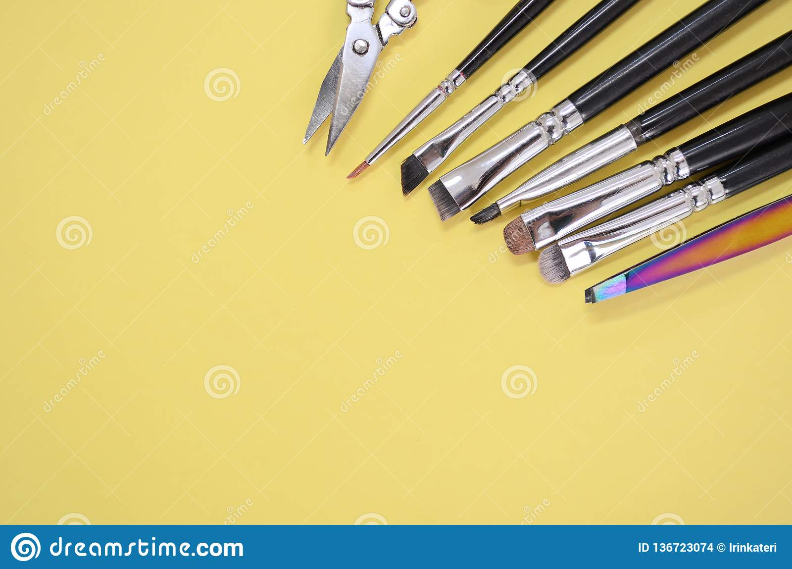 En uppsättning av olika borstar för makeupkonstnär och saxen ligger i ett hörn med copyspace för text på gul färg