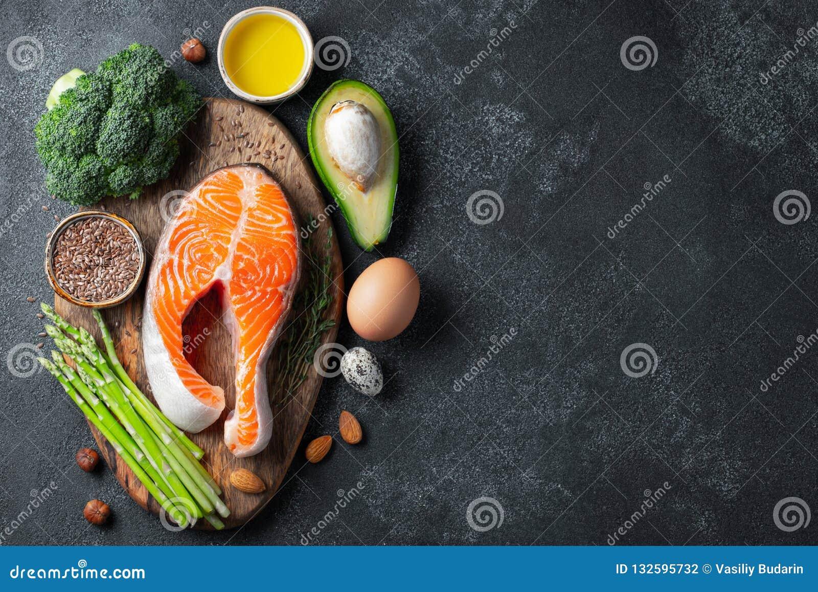 En uppsättning av sund mat för keto bantar på en mörk bakgrund Ny rå laxbiff med linfrö, broccoli, avokado, fega ägg