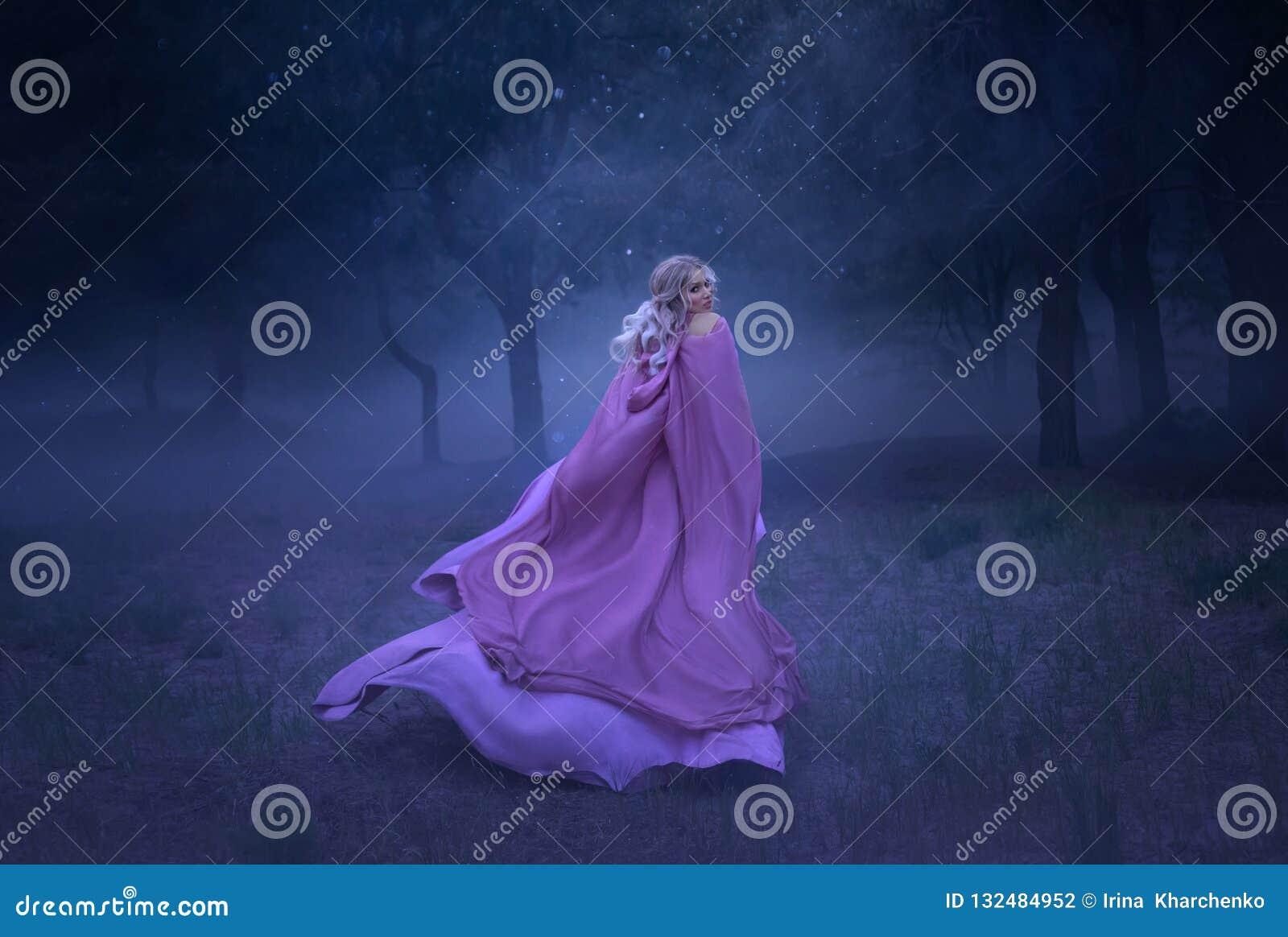 En ursnygg ung älvaprinsessa med blont hår, som flyr i en skog mycket av vit mist som är iklätt ett långt som är dyr