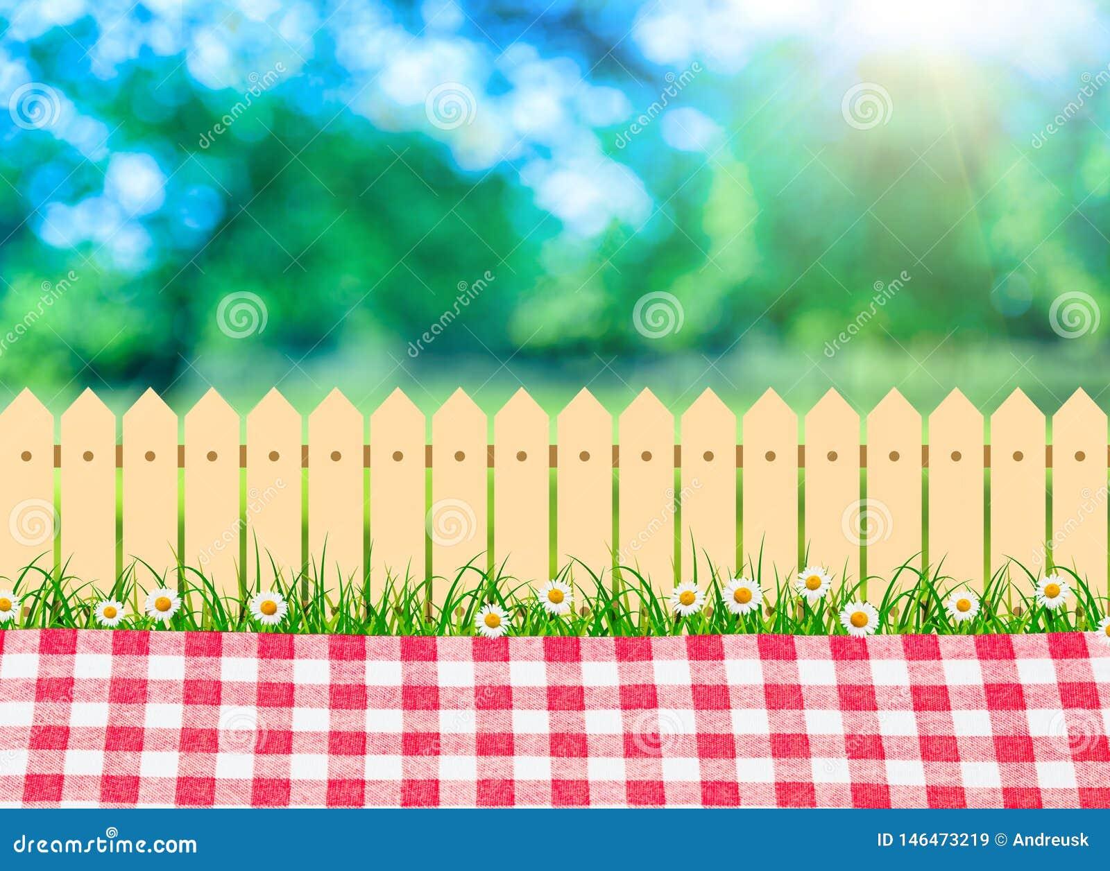 En utomhus- picknick, bordduk i trädgård och träträdgårdstaket