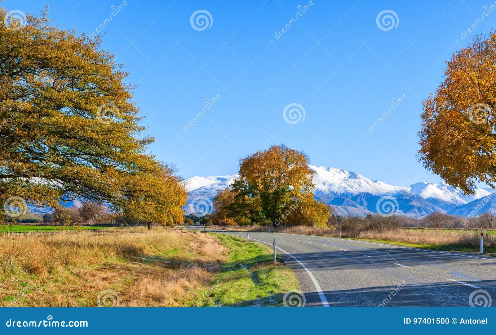 En väg med en härlig sikt nära snö-korkade berg på den soliga höstmorgonen, Canterbury, södra ö, Nya Zeeland