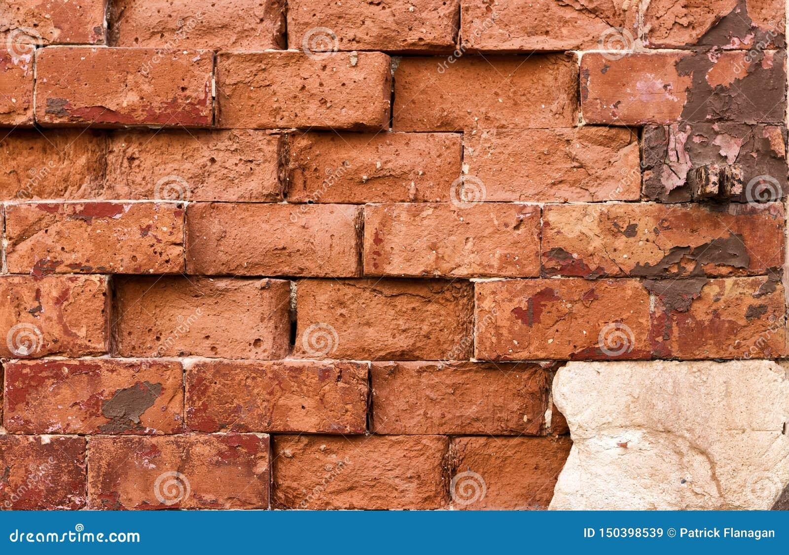 En vägg av haphazardly förlade röda tegelstenar