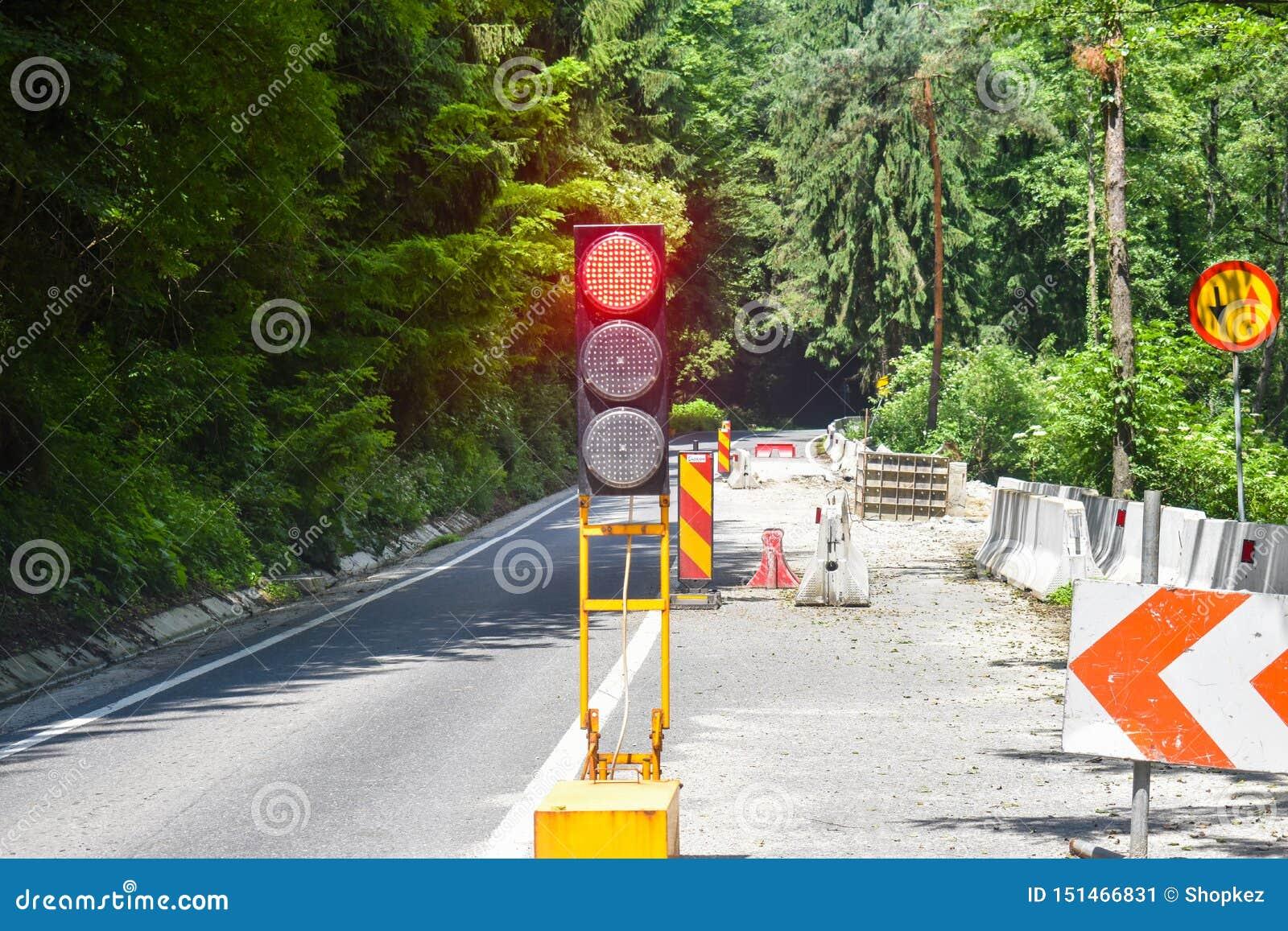En vägtrafikrörelse på vägen under reparationsarbete med röd trafikljus Skadad väg i underhåll