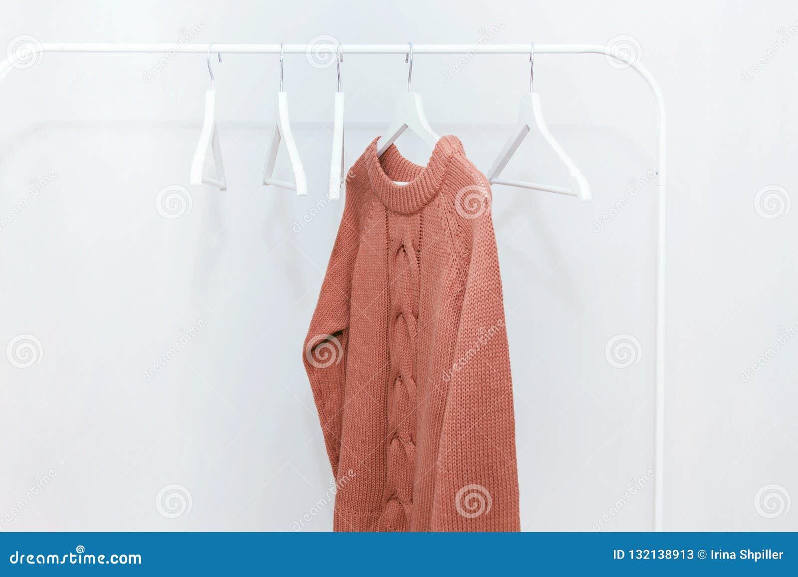 En varm tröja för orange pastellfärgad rät maska på hängare och många tomma hängare