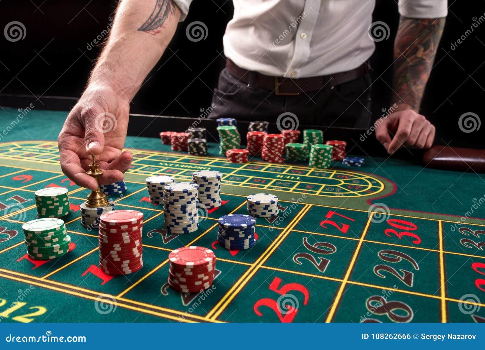 En vibrerande bild för närbild av den gröna kasinotabellen med rouletten, med händerna av croupier och mångfärgade chiper
